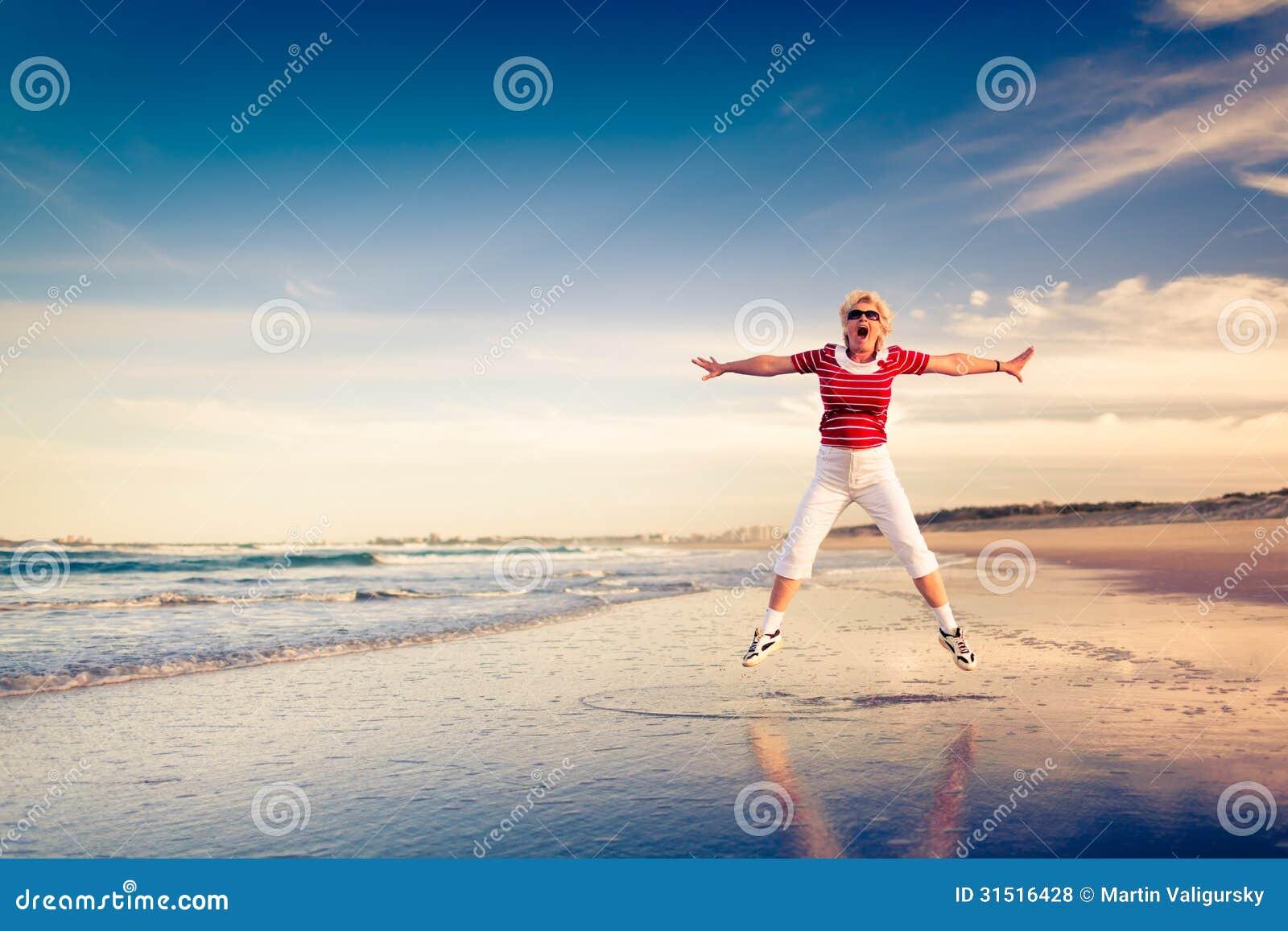 Starsza kobieta cieszy się plażowego wakacyjnego doskakiwanie w powietrzu