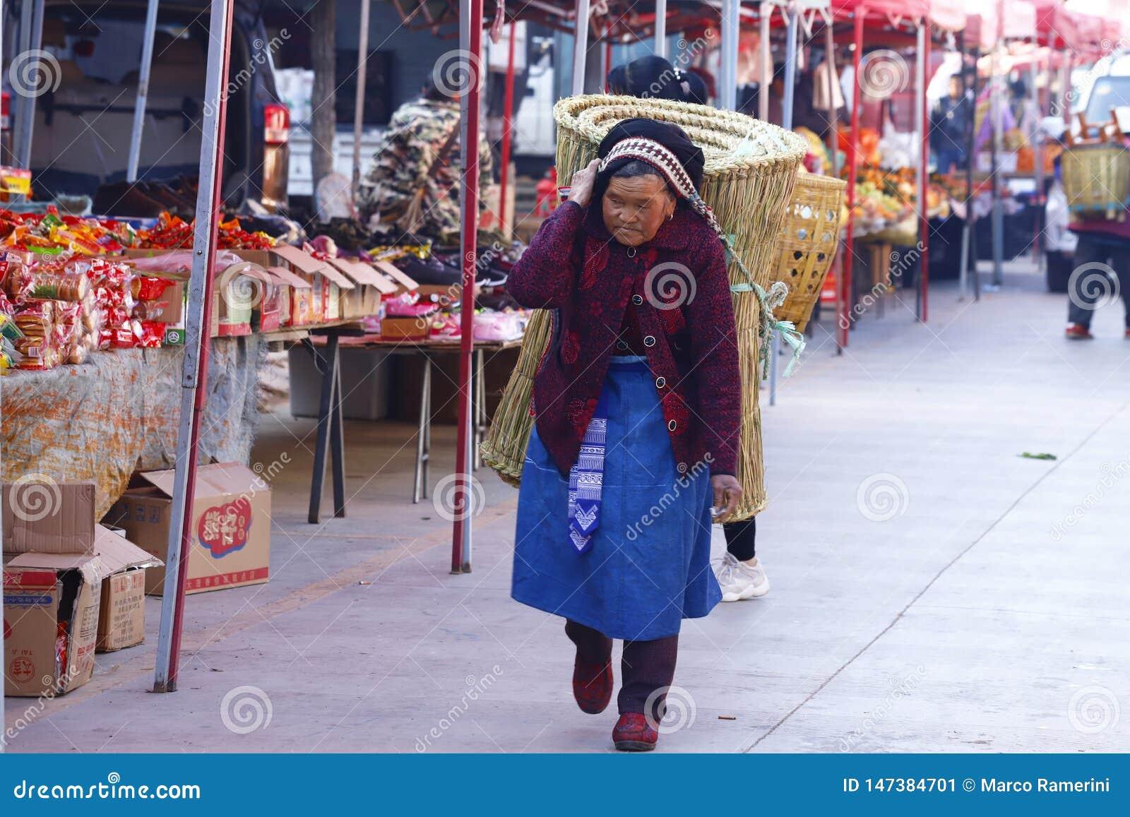 Starsza kobieta niesie dużego kosz przy Shaxi rynkiem w Yunnan, Chiny