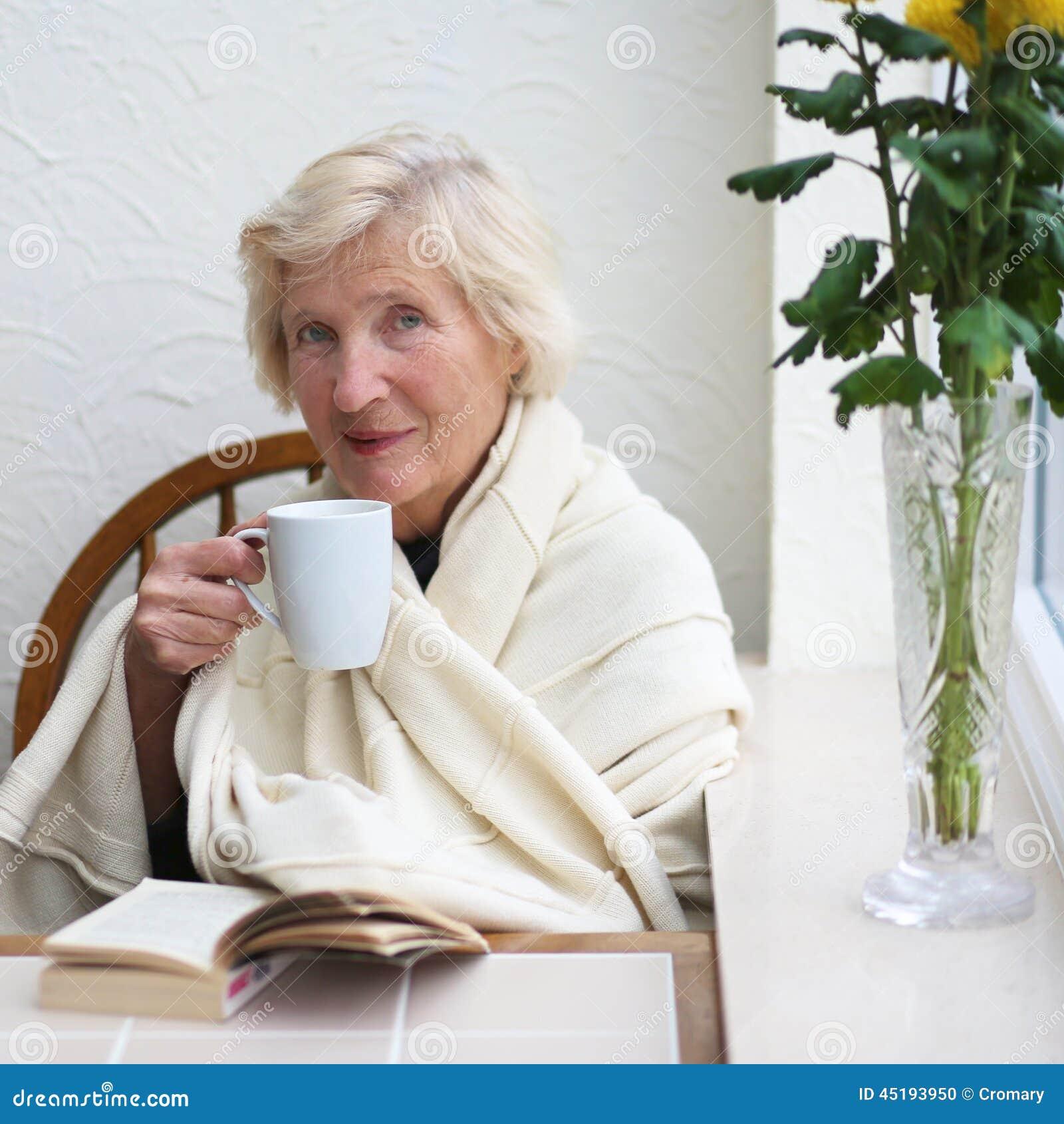 Starsza kobieta pije herbaty indoors