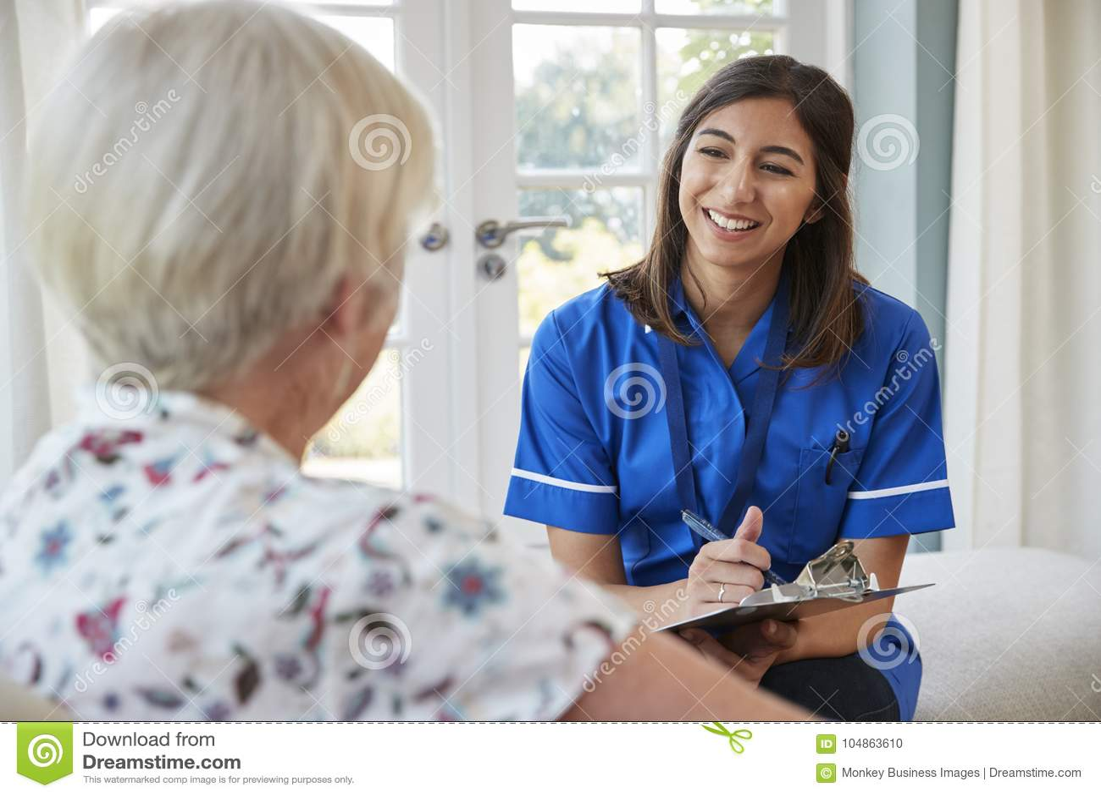 Starsza kobieta siedzi w domu z opieki pielęgniarką bierze notatki