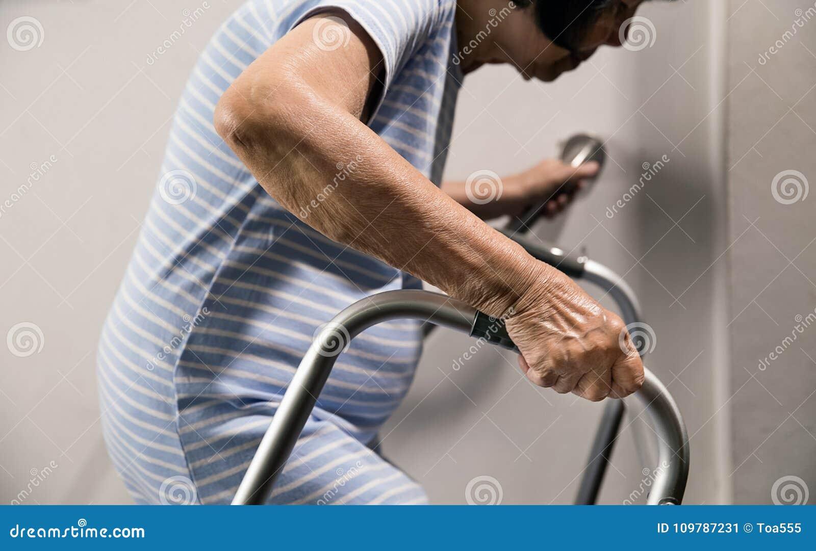 Starsza kobieta trzyma dalej poręcz i piechura dla bezpieczeństwa