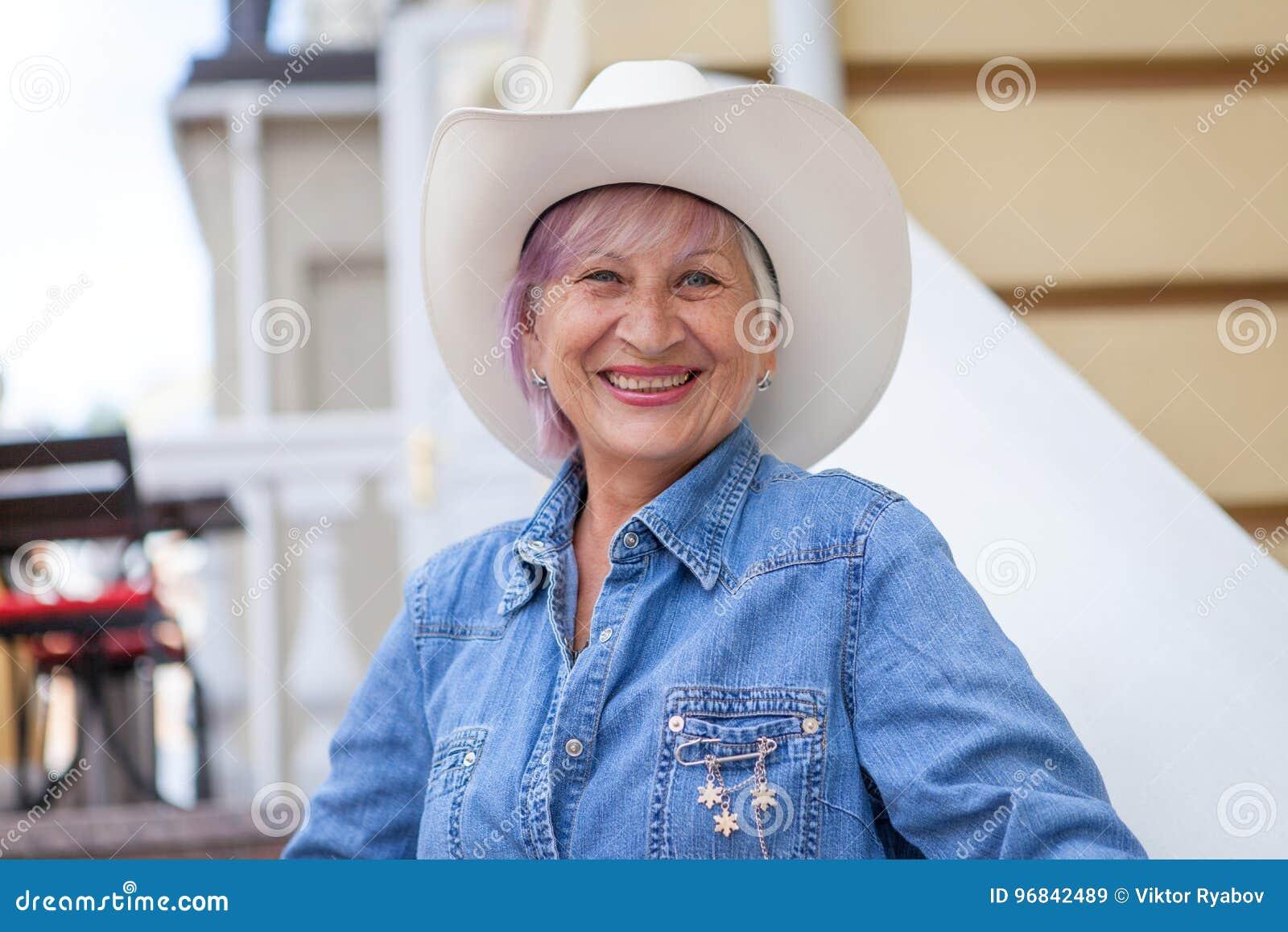 Starsza kobieta w kowbojskim kapeluszu, patrzeje kamerę i ono uśmiecha się na na wolnym powietrzu