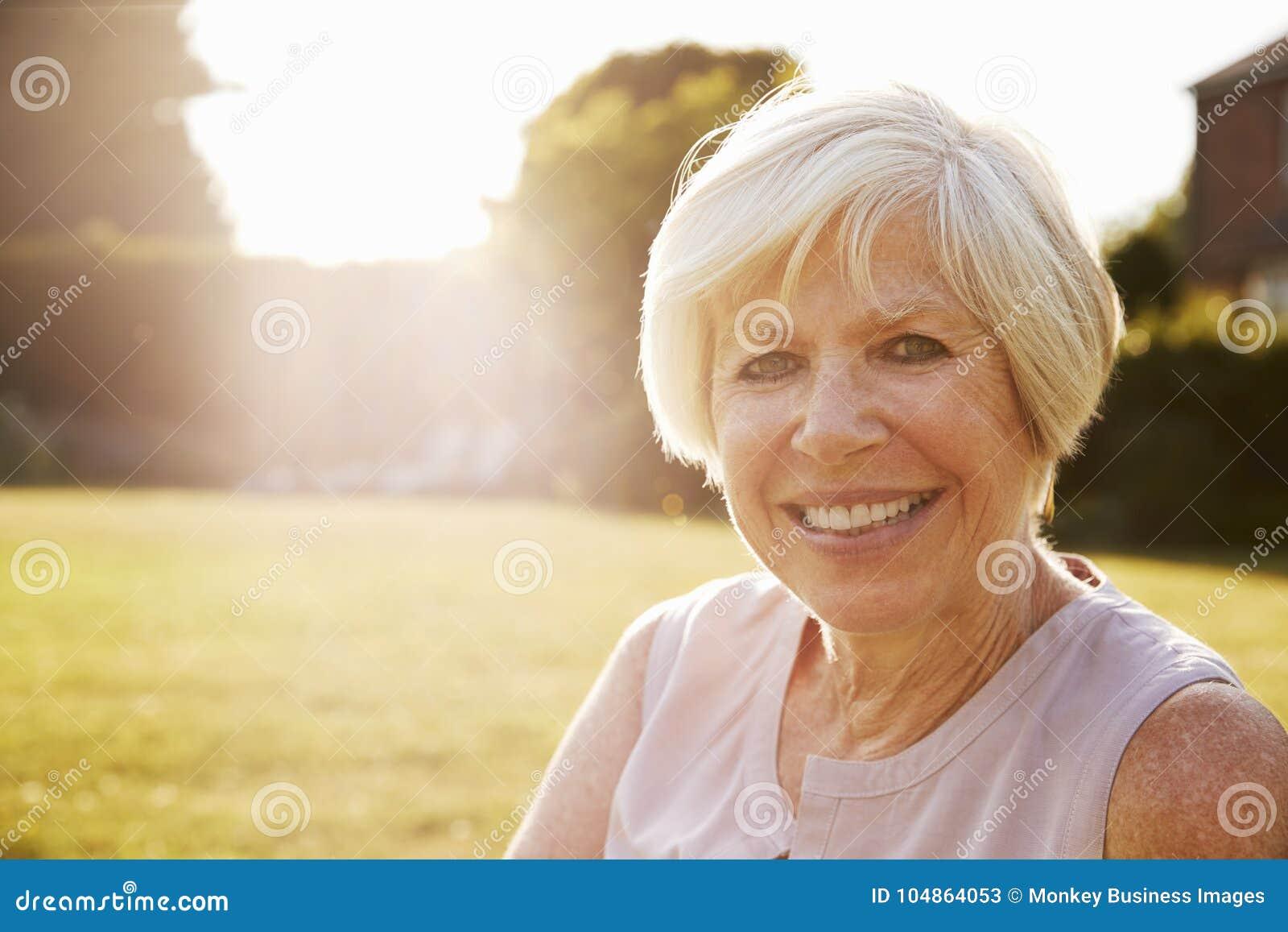 Starsza kobieta w ogródzie, ono uśmiecha się kamera, zamyka up