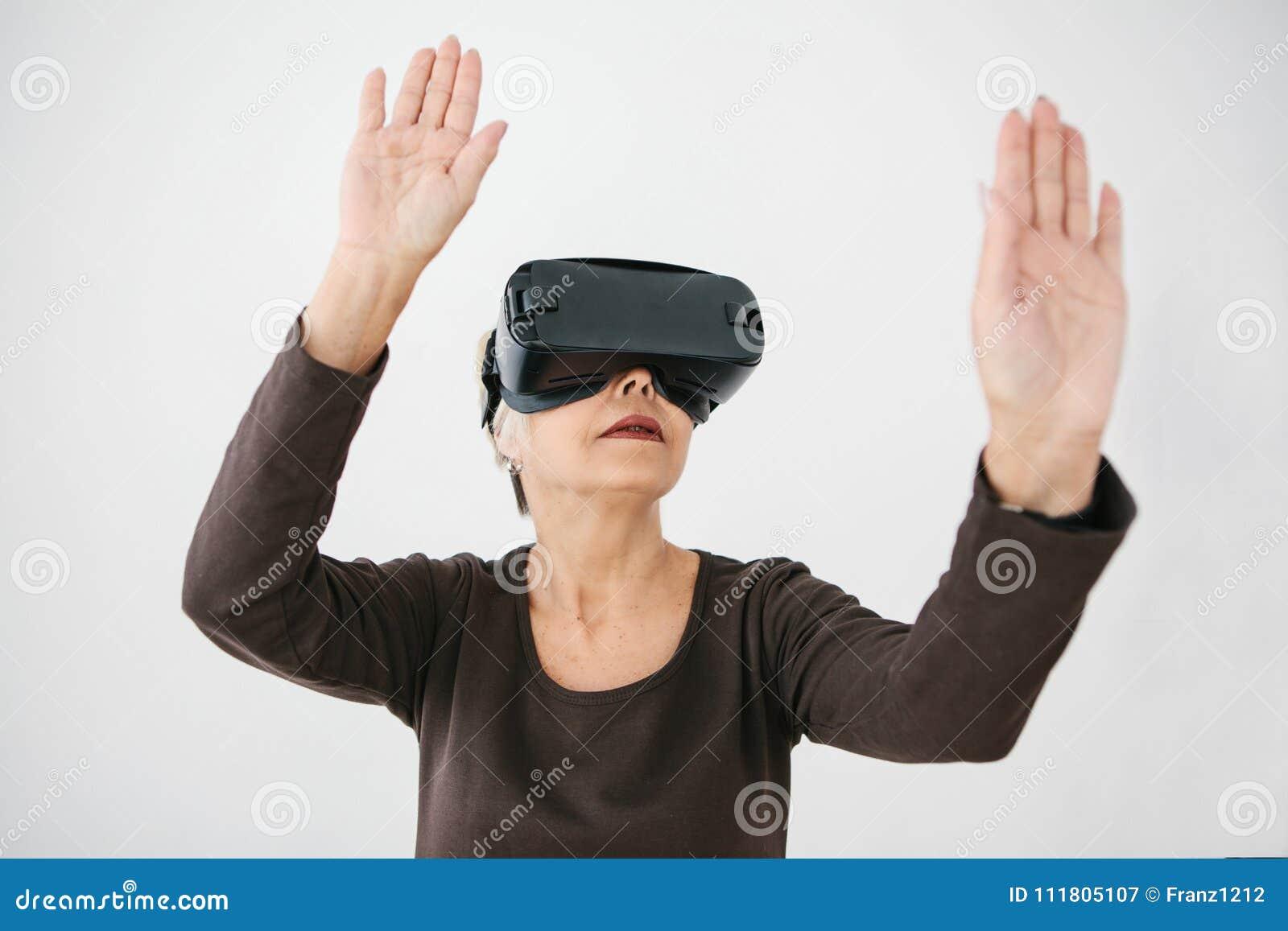 Starsza kobieta w rzeczywistość wirtualna szkłach Starsza osoba używa nowożytną technologię