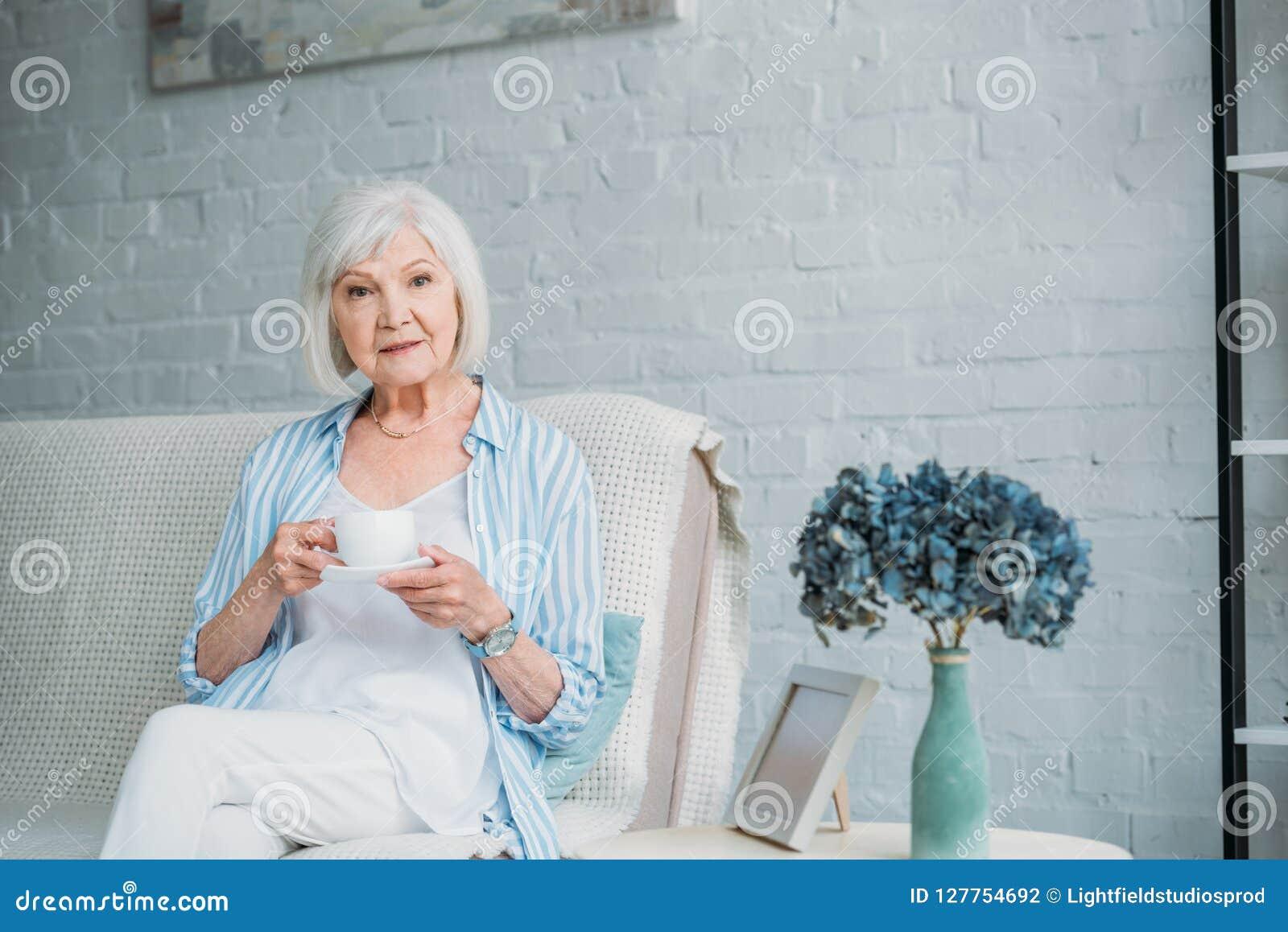 Starsza kobieta z filiżanką aromatyczny kawowy odpoczywać na kanapie