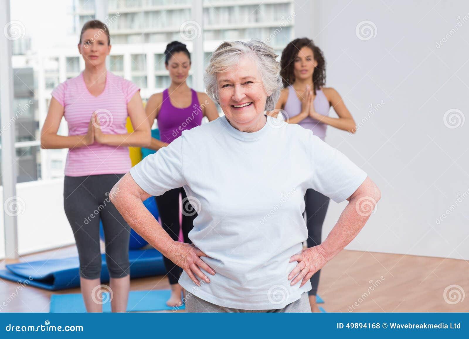 Starsza kobieta z rękami na modnej pozyci w gym