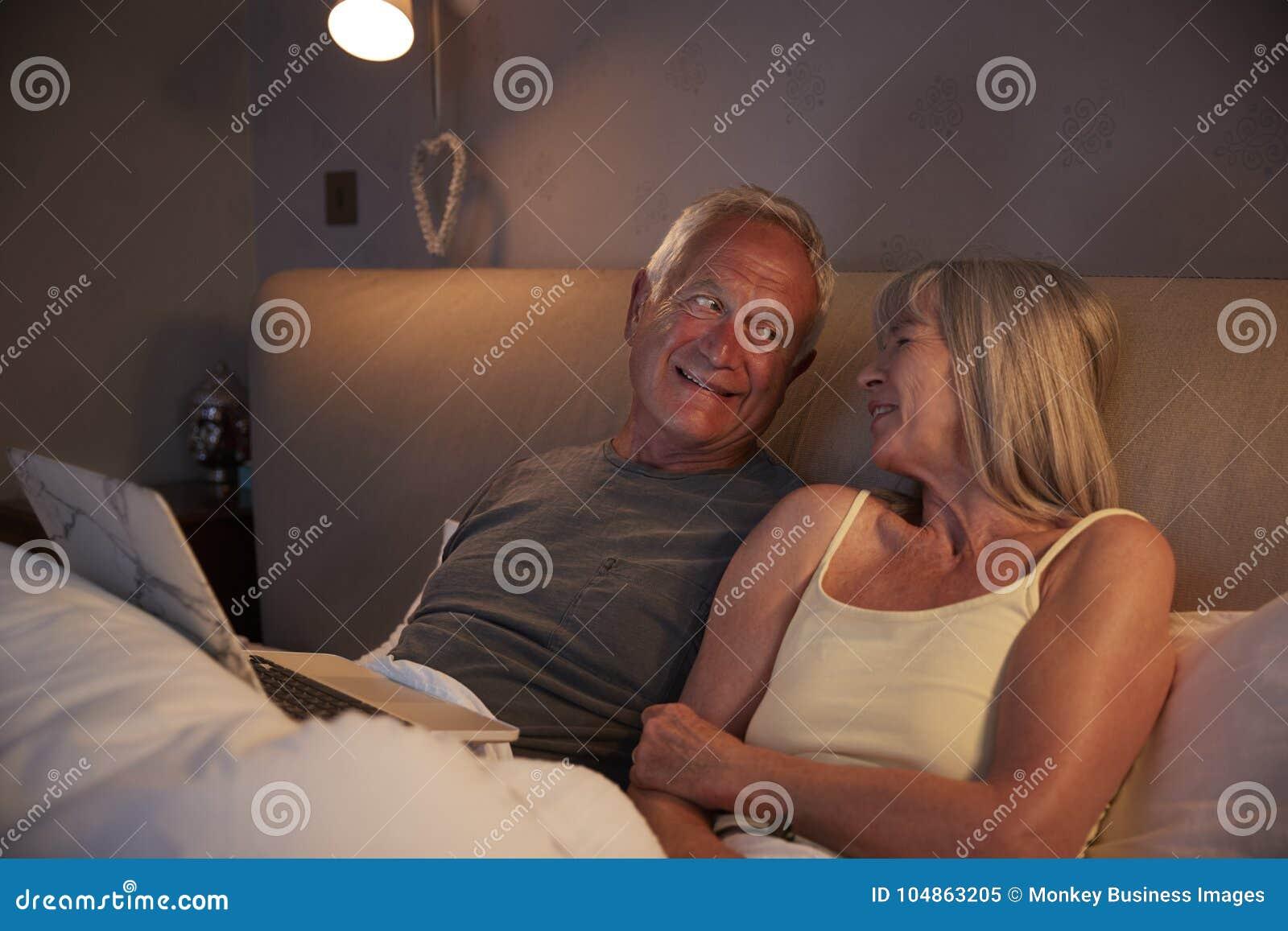 Starsza para Jest ubranym piżamy Kłama W Łóżkowym Patrzeje laptopie