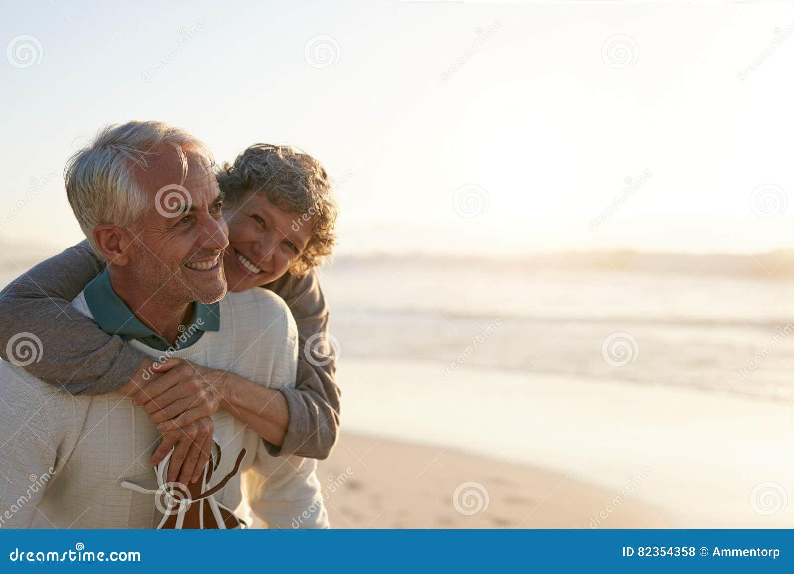 Starsza para ma zabawę przy plażą