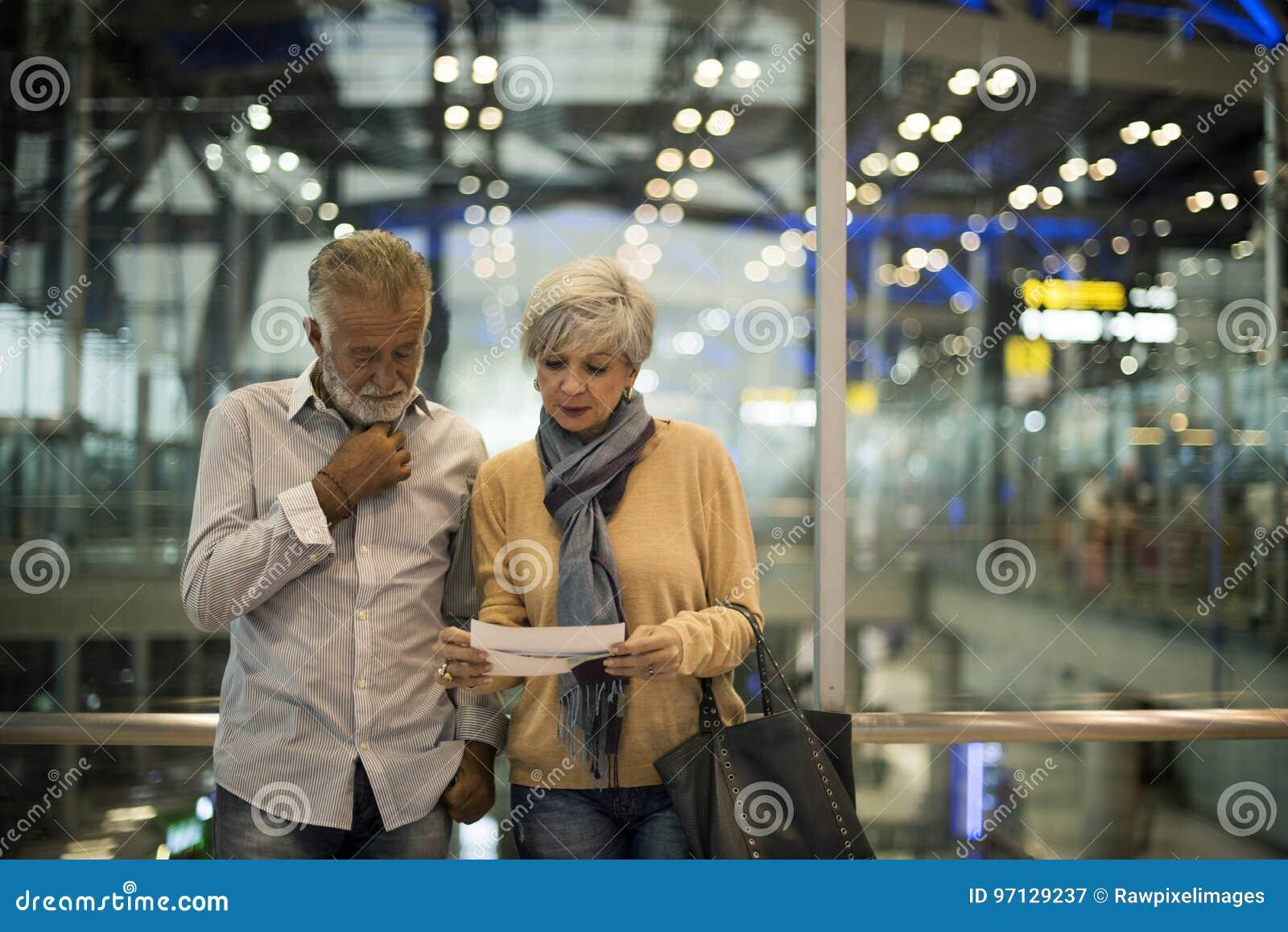 Starsza para podróżuje wpólnie w lotniskowej scenie