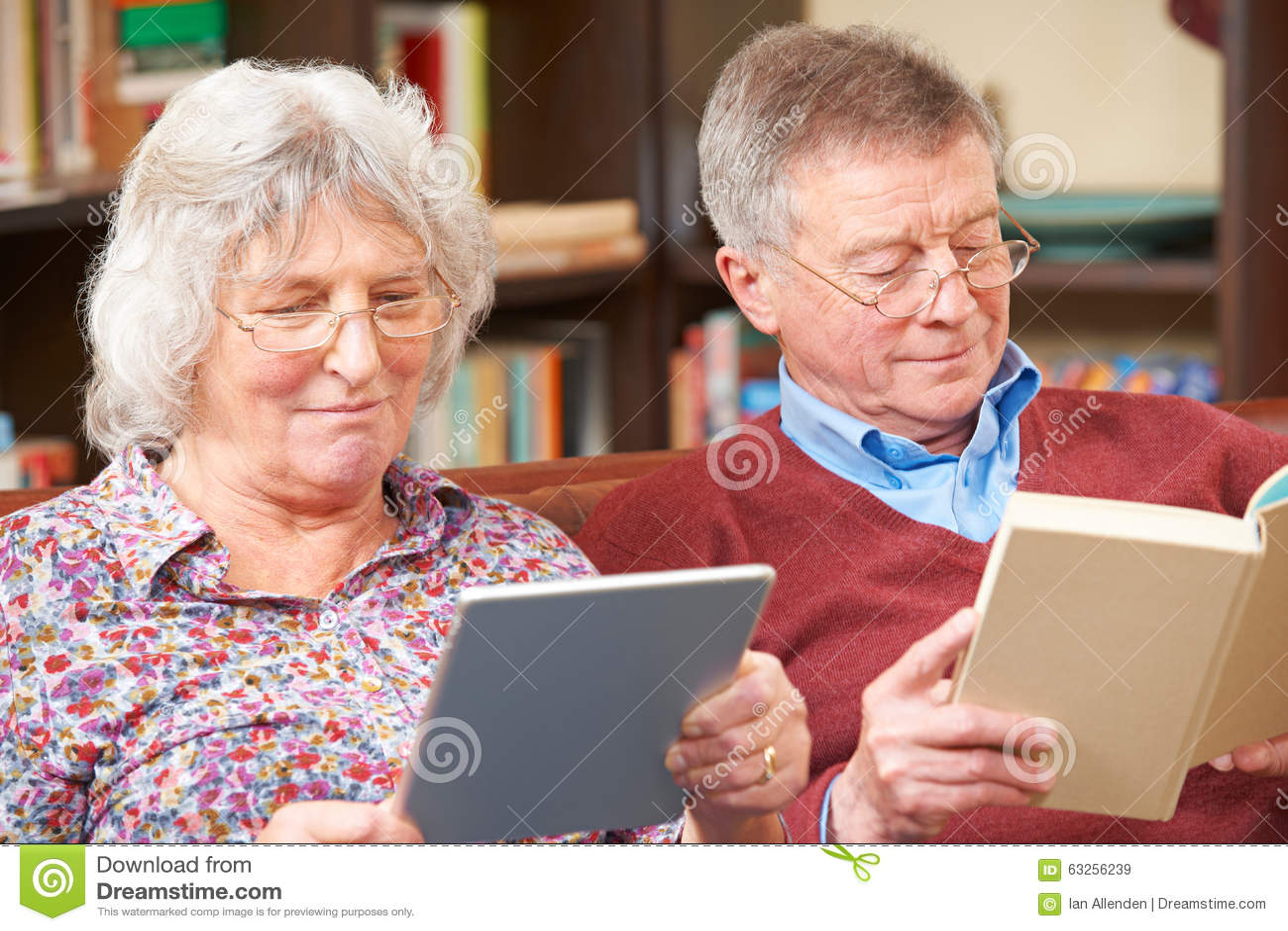 Starsza para Używa Cyfrowej pastylkę I Czytelniczą książkę