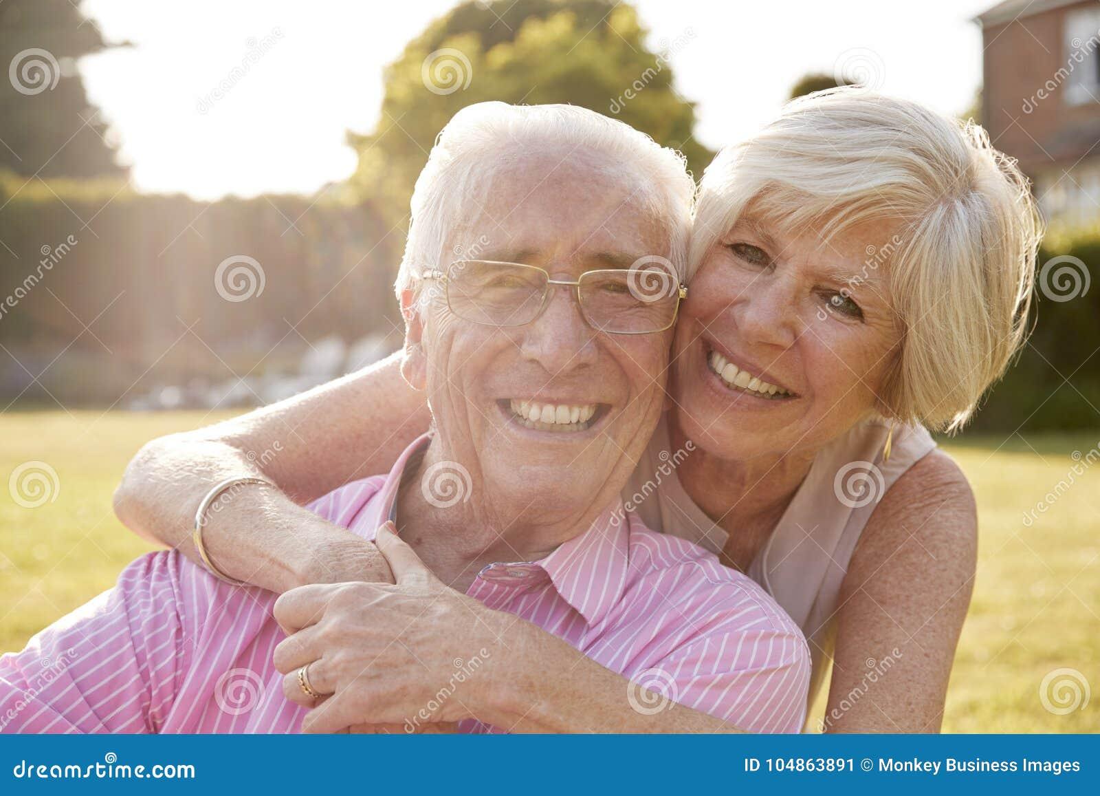 Starsza para w ogródzie, ono uśmiecha się przy kamerą, zamyka up