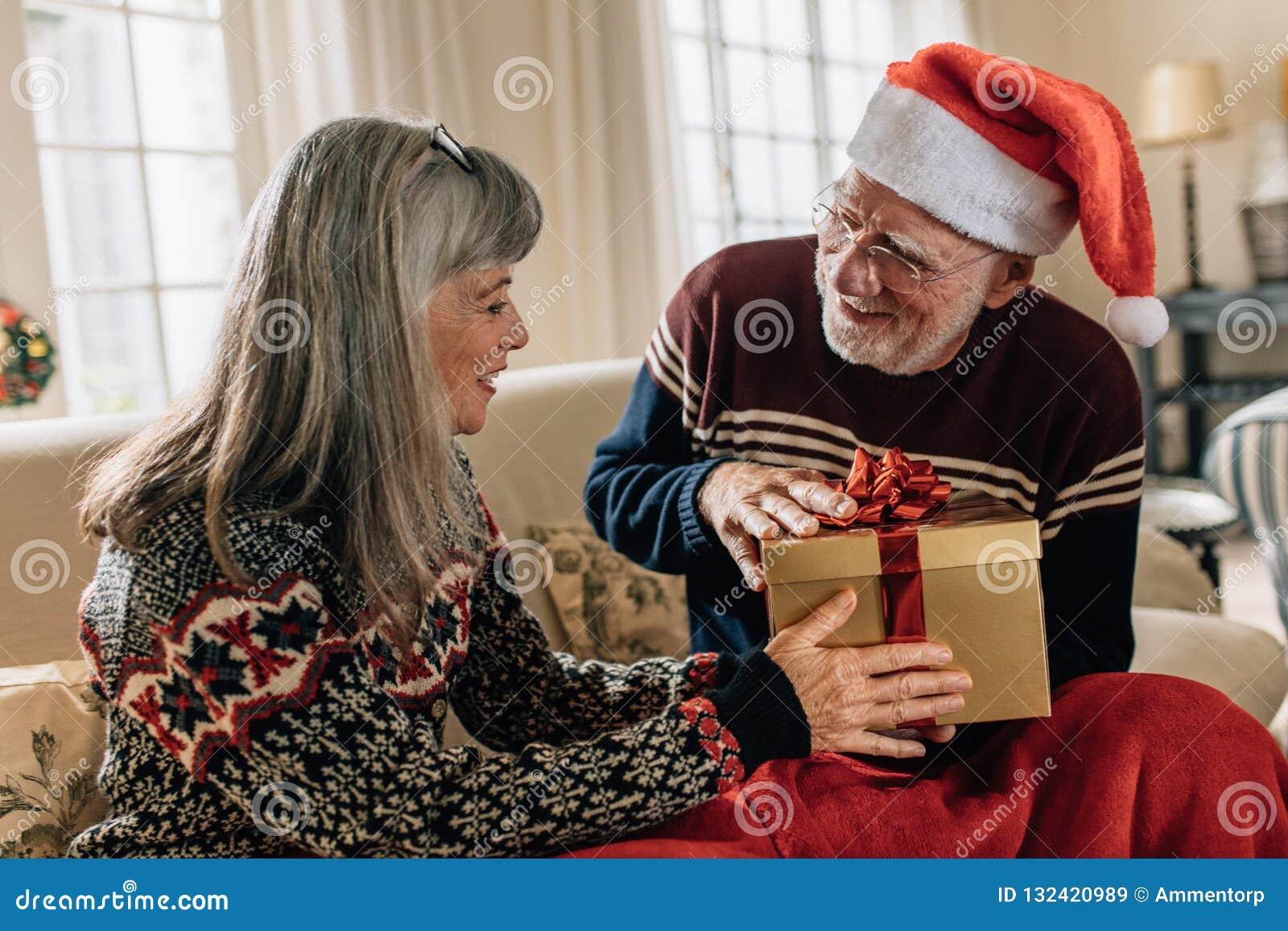 Starsza para wymienia boże narodzenie prezenty w domu