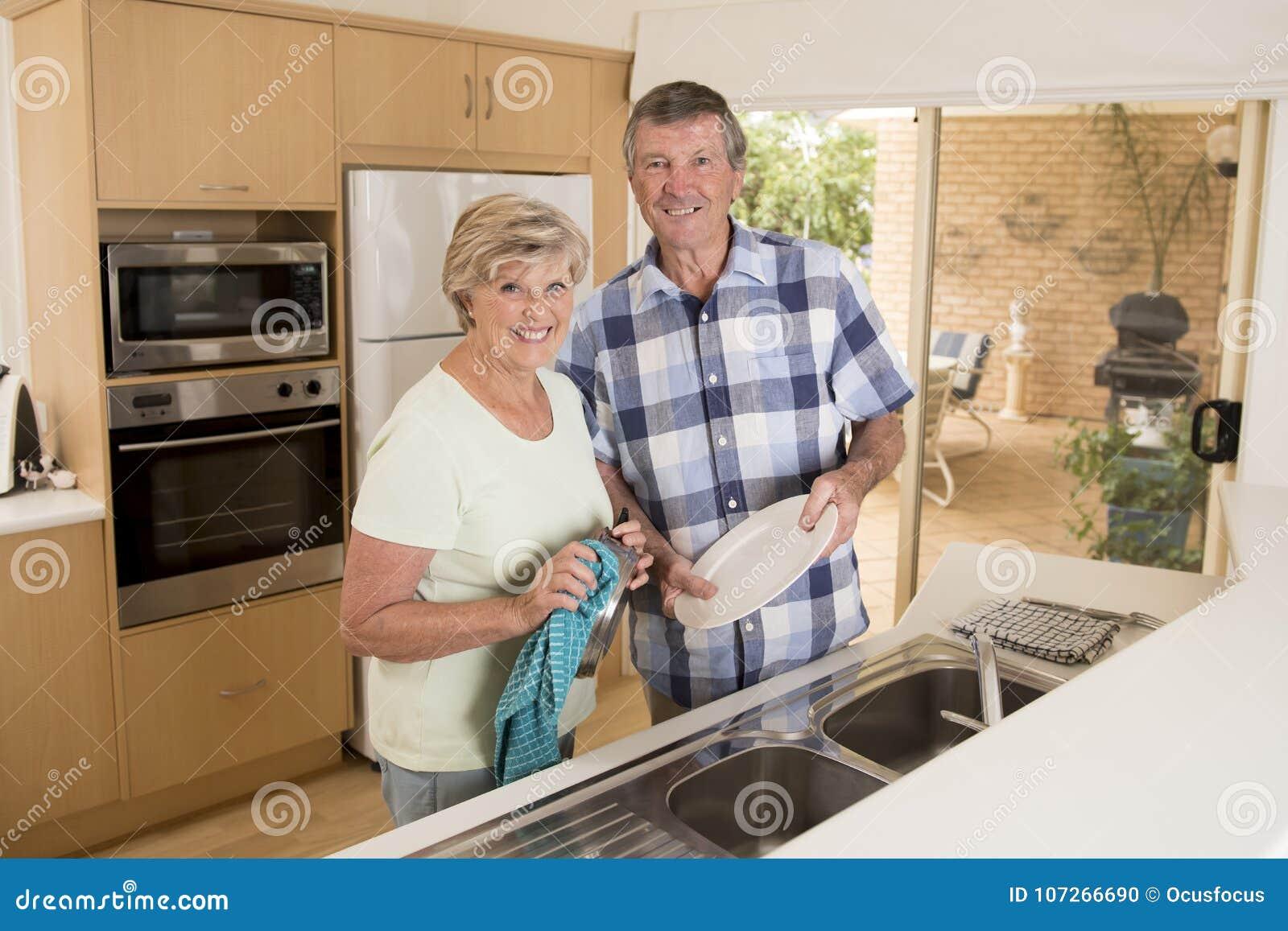 Starsza piękna wiek średni para uśmiecha się szczęśliwego kuchennego domycie w domu patrzeje cukierki wpólnie wokoło 70 lat naczy