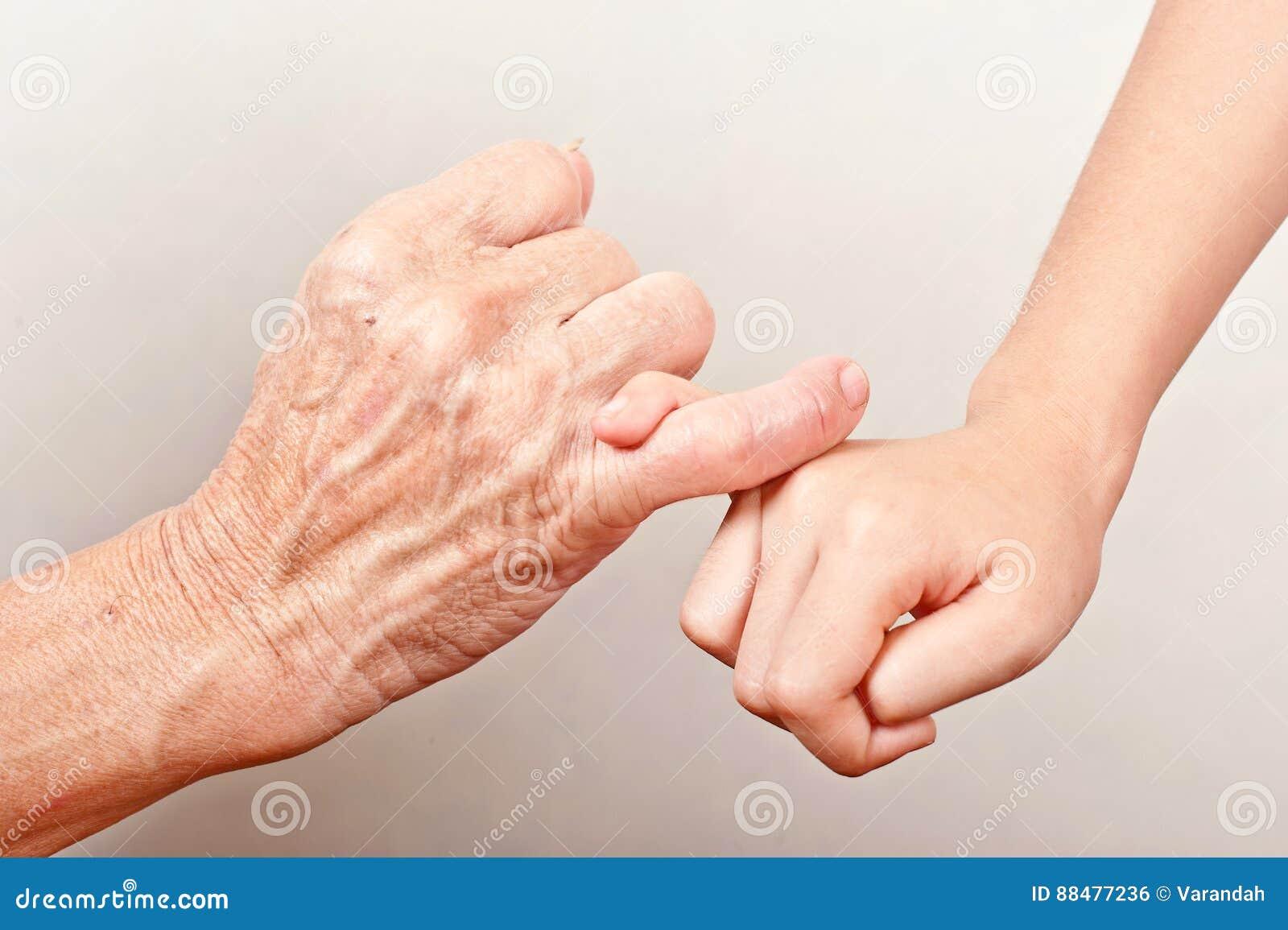 Starsza starej kobiety ręka, dziecko i wręczamy haczyć ich palce