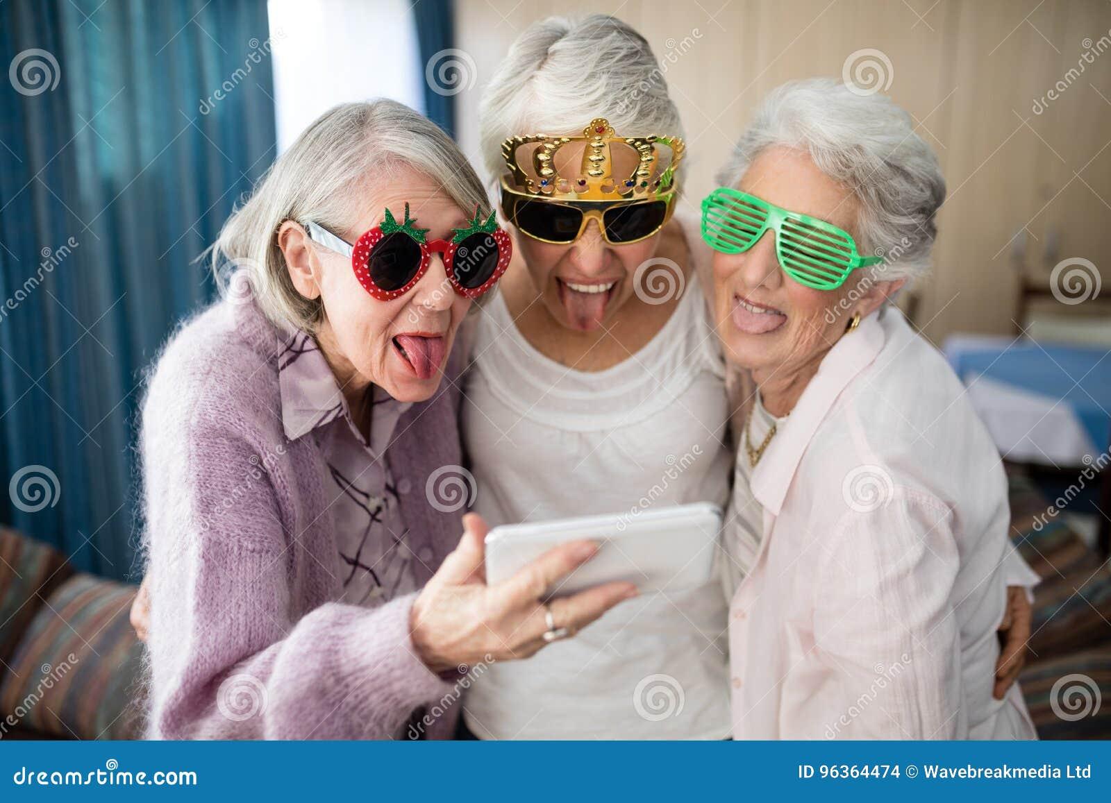 Starsze kobiety jest ubranym odkrywczość szkła robi twarzy podczas gdy brać selfie