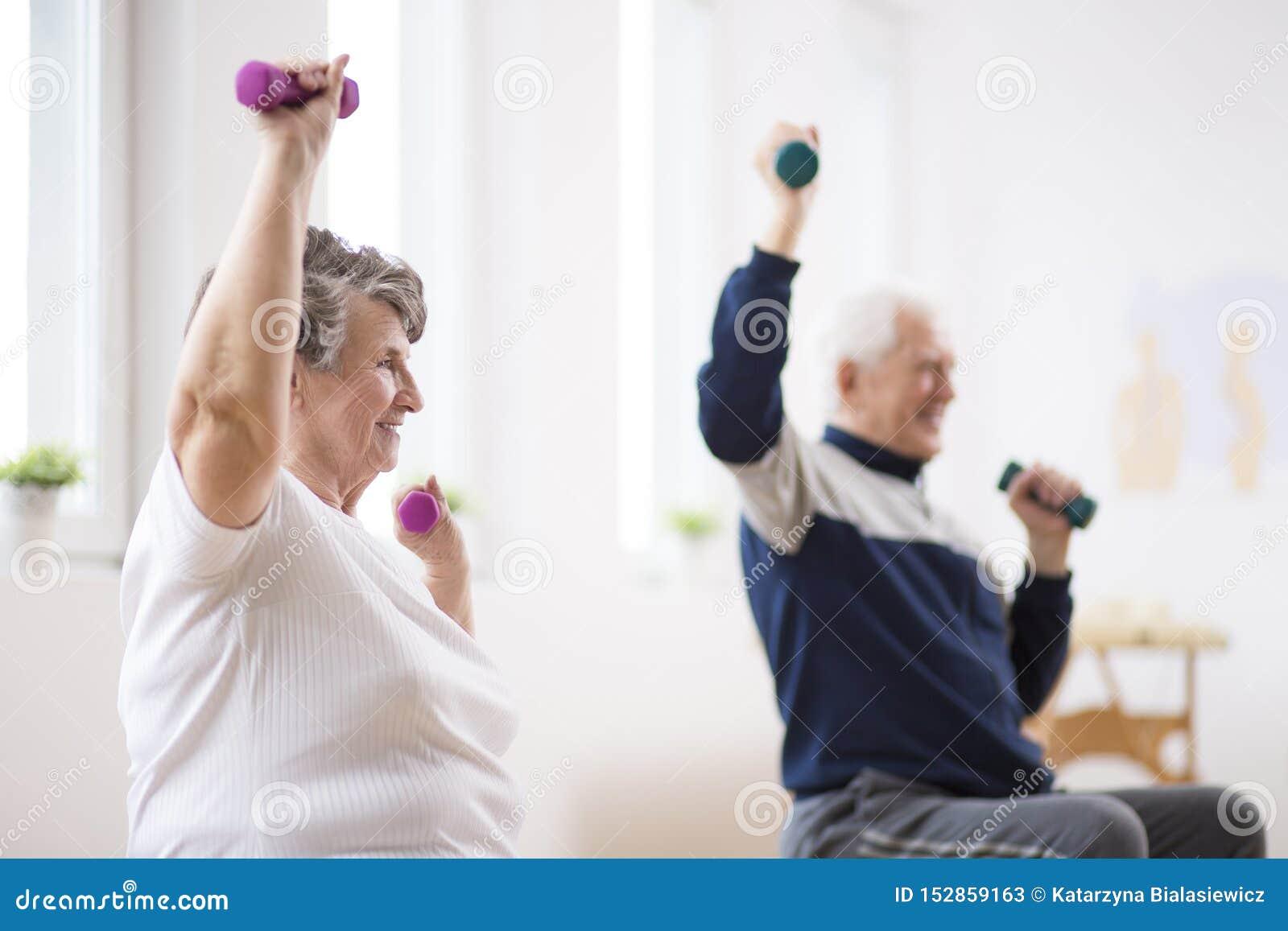 Starsze osoby obsługują i kobieta ćwiczy z dumbbells podczas fizjoterapii sesji przy szpitalem