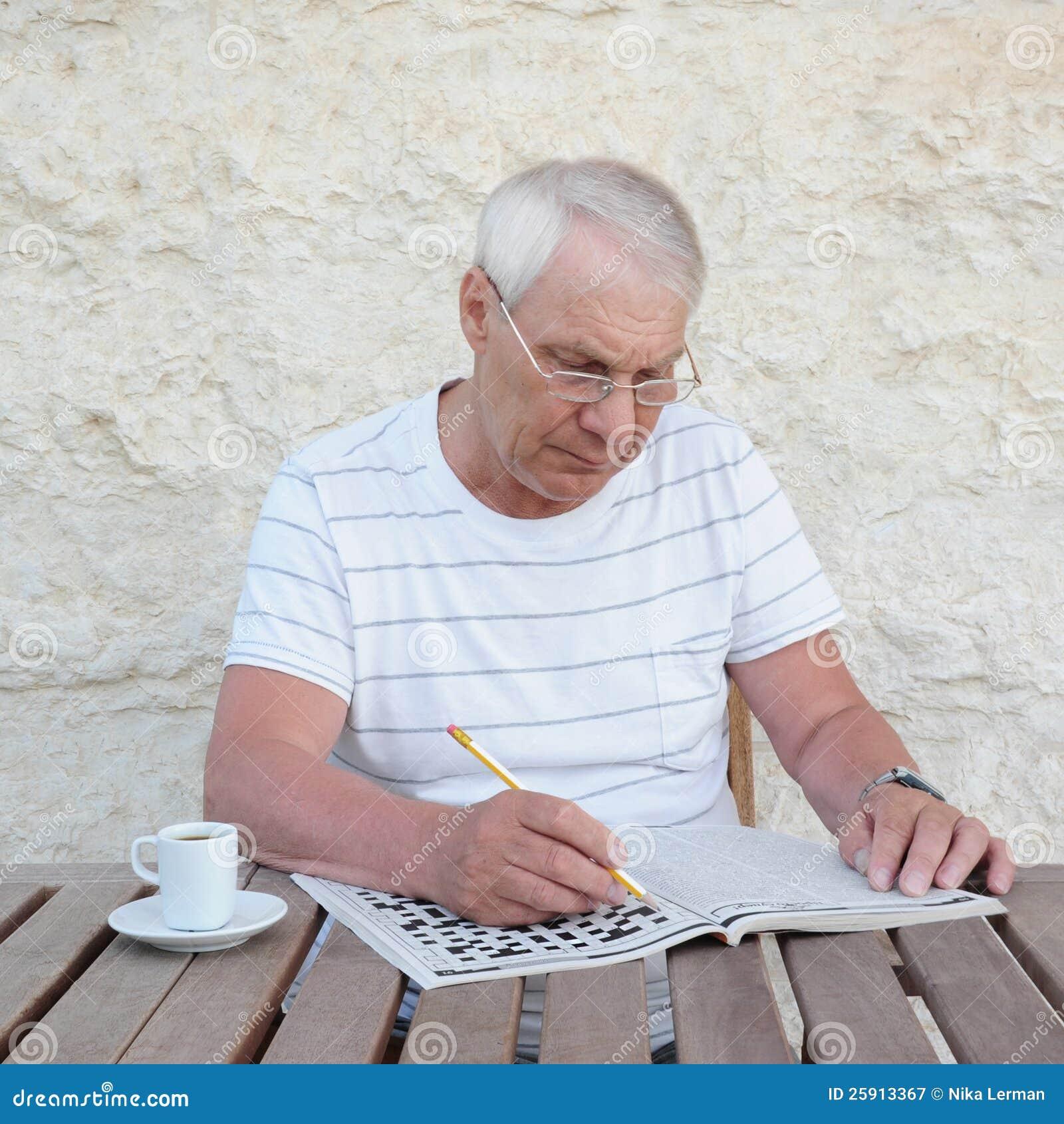 Starsze osoby obsługują z crossword łamigłówką