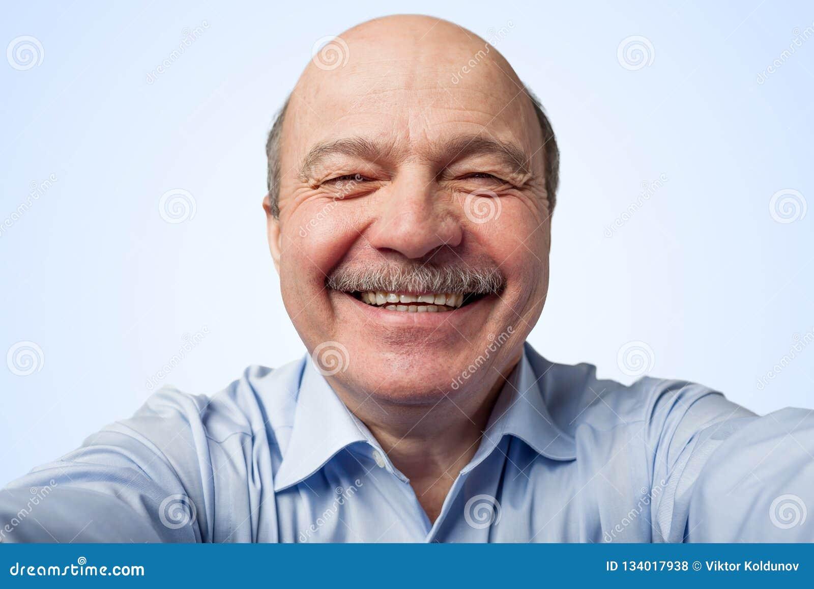 Starsze osoby trzyma smartphone obsługują z wąsy i robią selfie, ono uśmiecha się szeroko