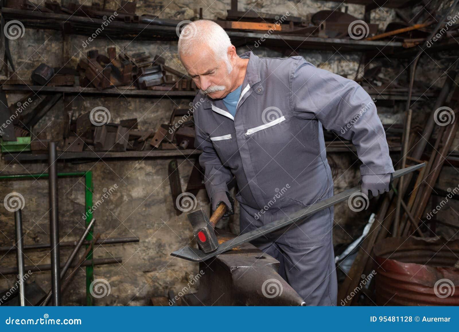 Starszego blacksmith skucia stopiony metal