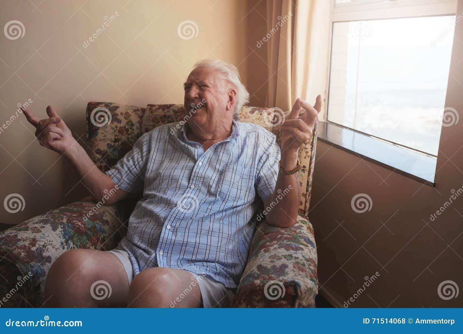 Starszego mężczyzna obsiadanie w ręki krześle