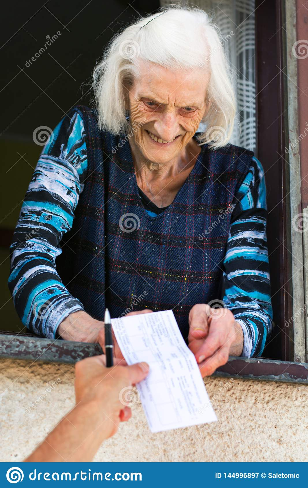 Starszej kobiety emerytura odbiorczy czek w domu
