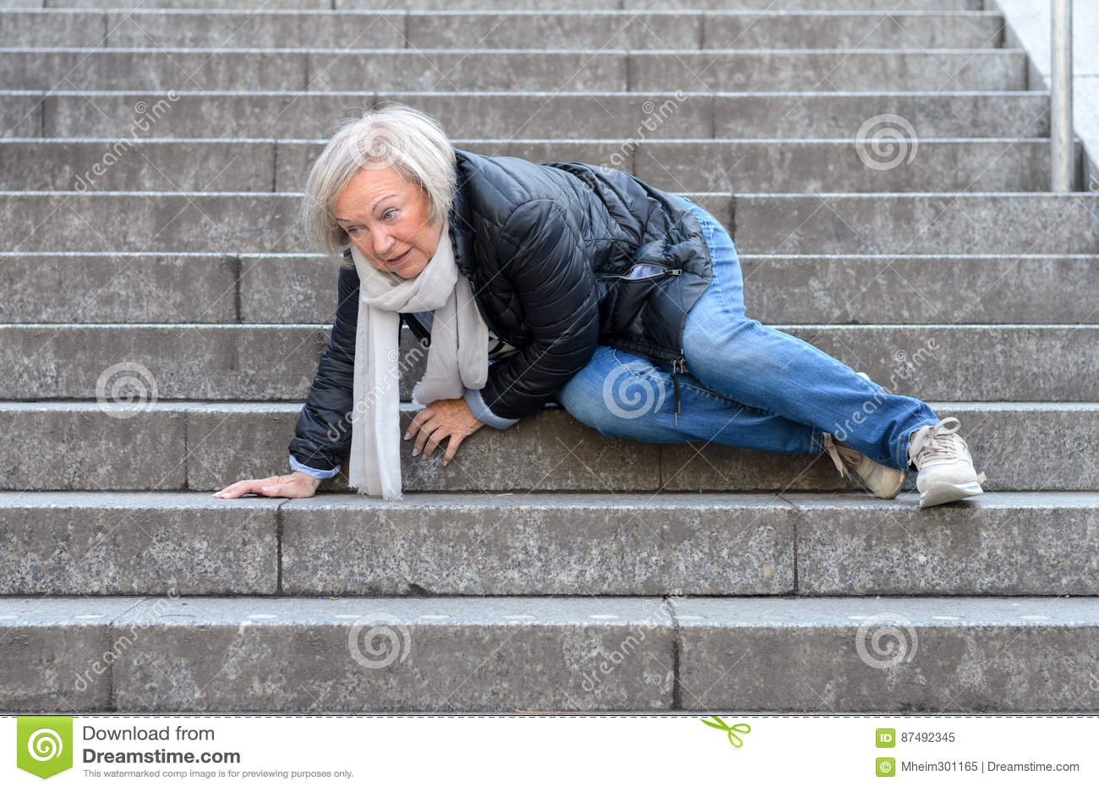 Starszej kobiety puszka spada kamień kroczy outdoors