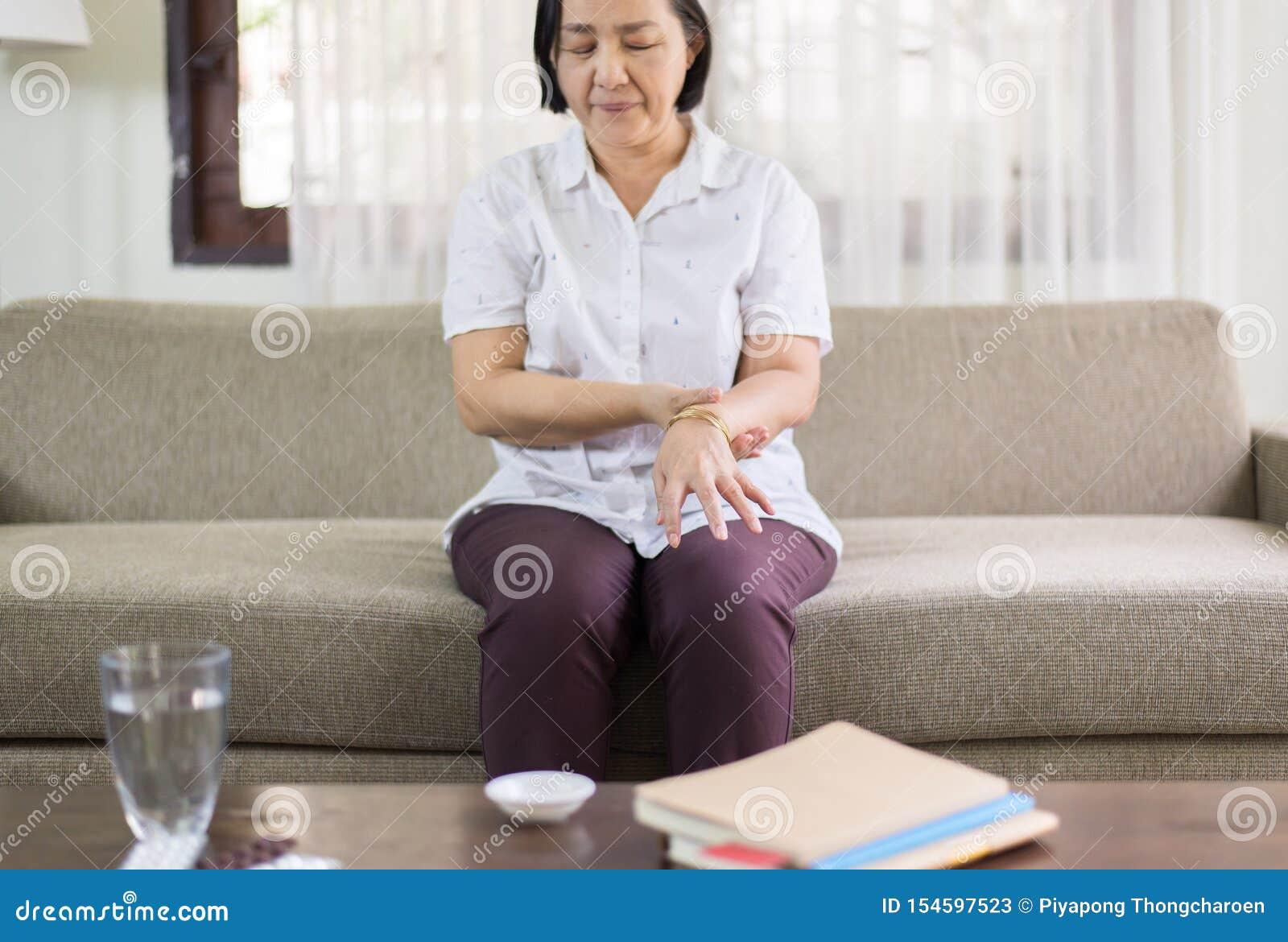 Starszy azjatykci kobiety cierpienie z Parkinson choroby objawami na rękach