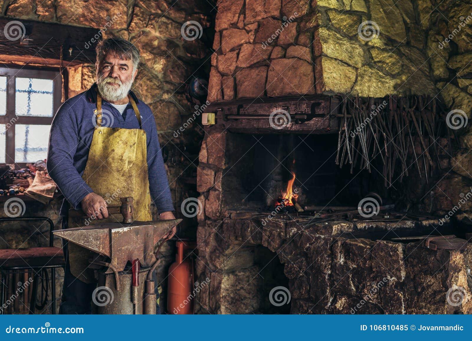 Starszy blacksmith kuźni żelazo