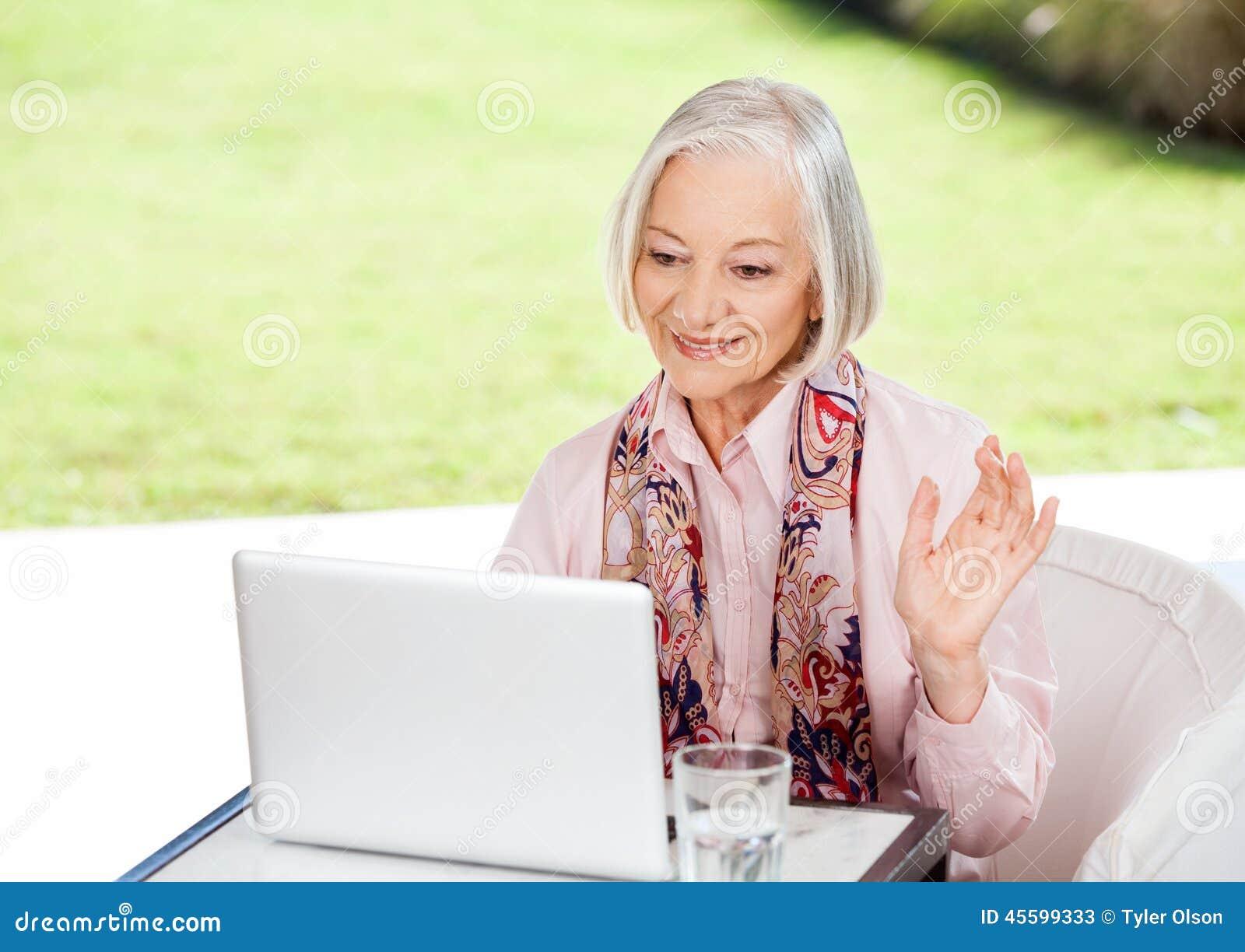 Starszy kobiety falowanie Podczas gdy Wideo konferencja Dalej