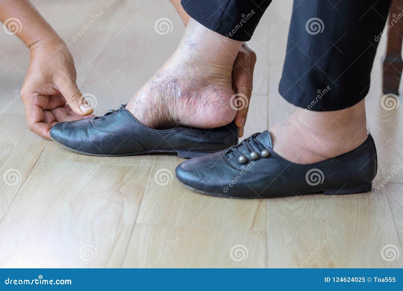 Starszy kobiety kładzenie na butach z opieka dawcą