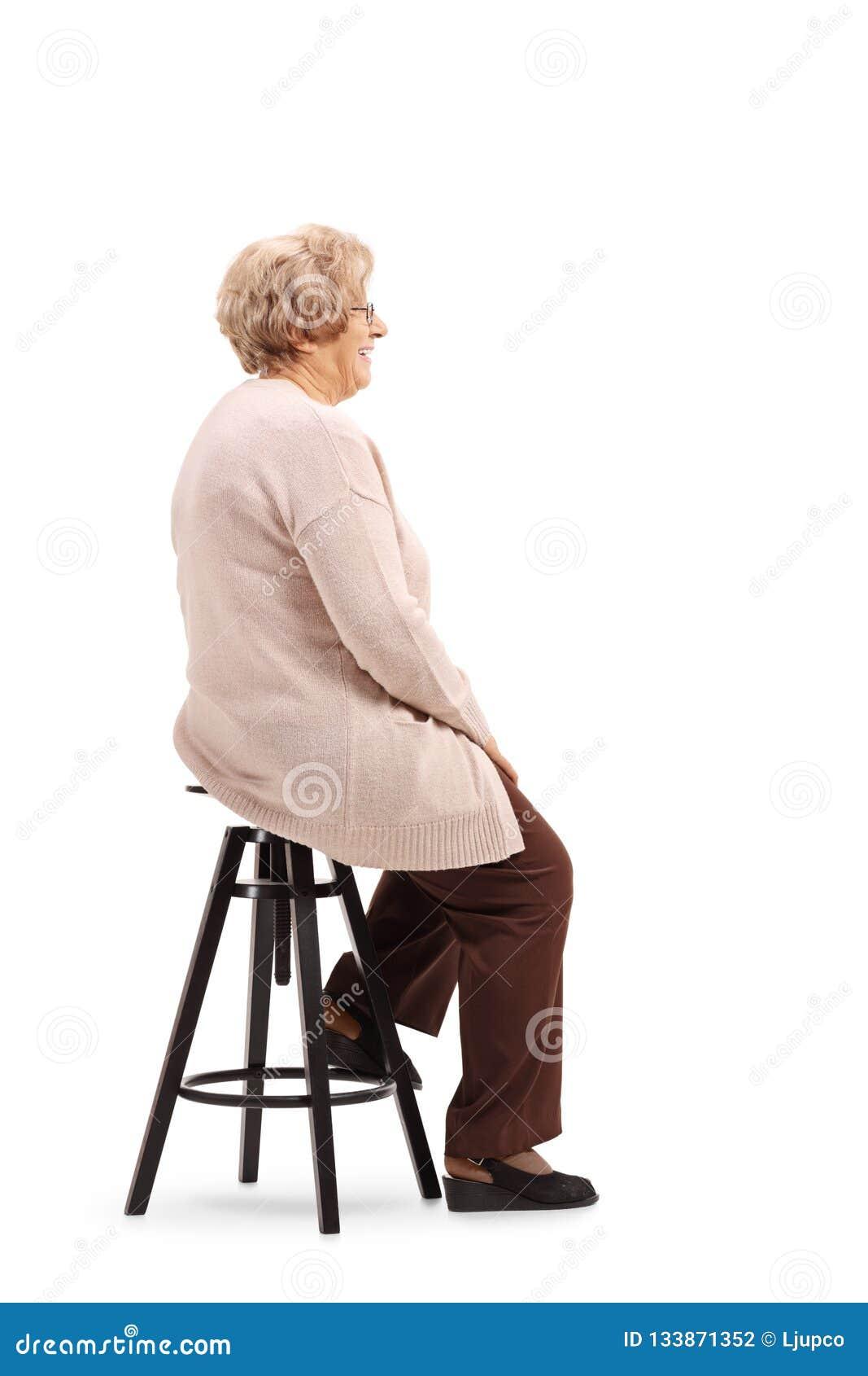 Starszy kobiety obsiadanie na stolec pozować i krześle
