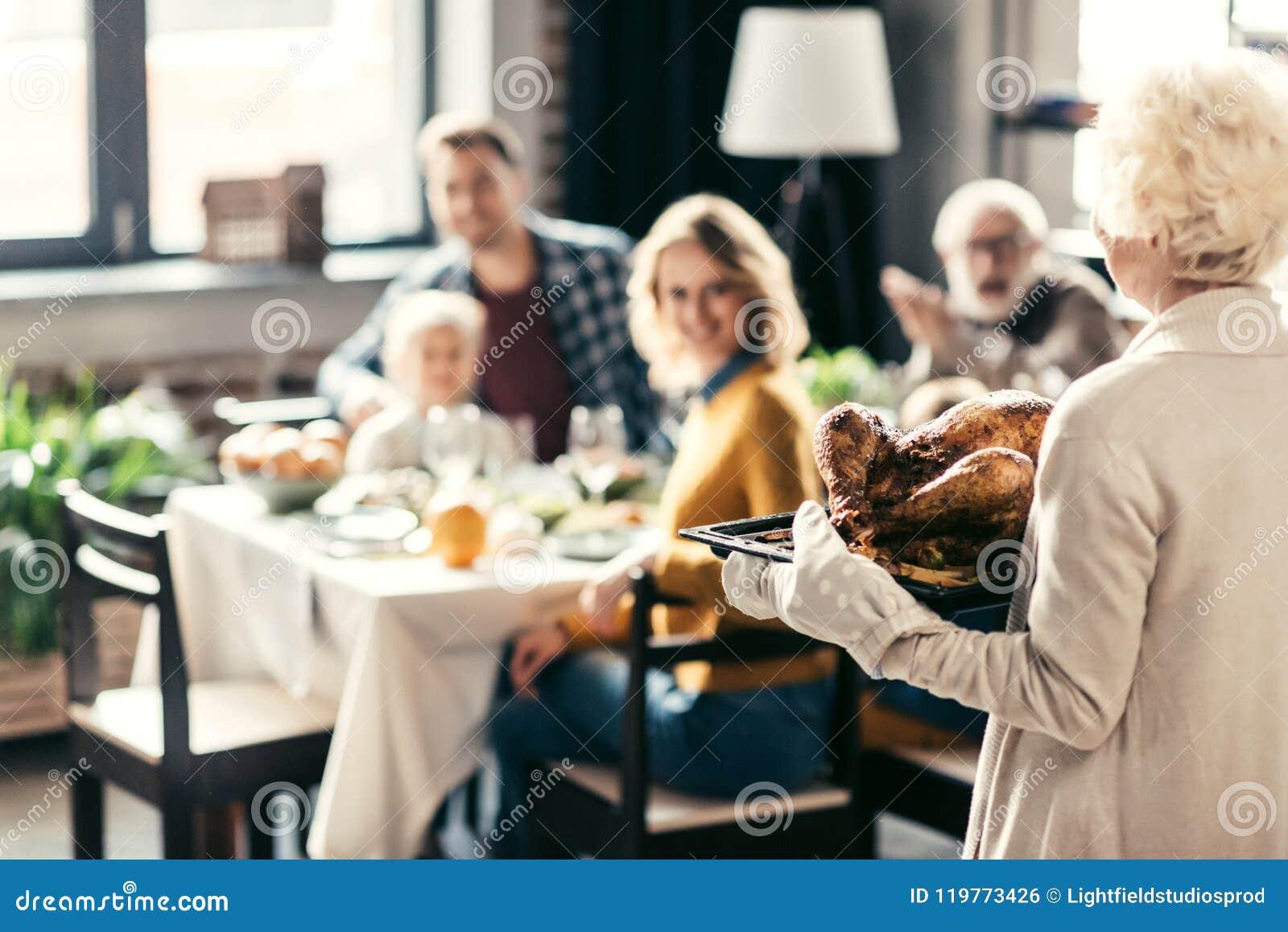 Starszy kobiety przewożenia dziękczynienia indyk dla wakacyjnego gościa restauracji