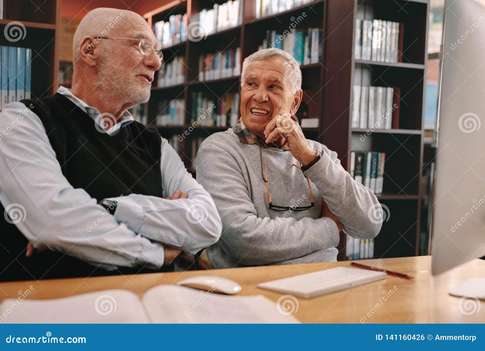 Starszy mężczyźni siedzi w opowiadać i sali lekcyjnej