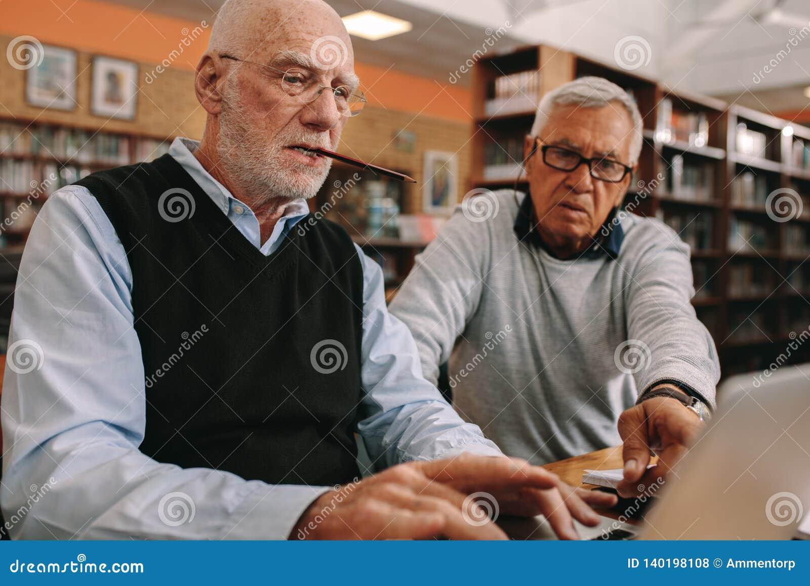 Starszy mężczyźni siedzi w sali lekcyjnej pracuje na laptopie