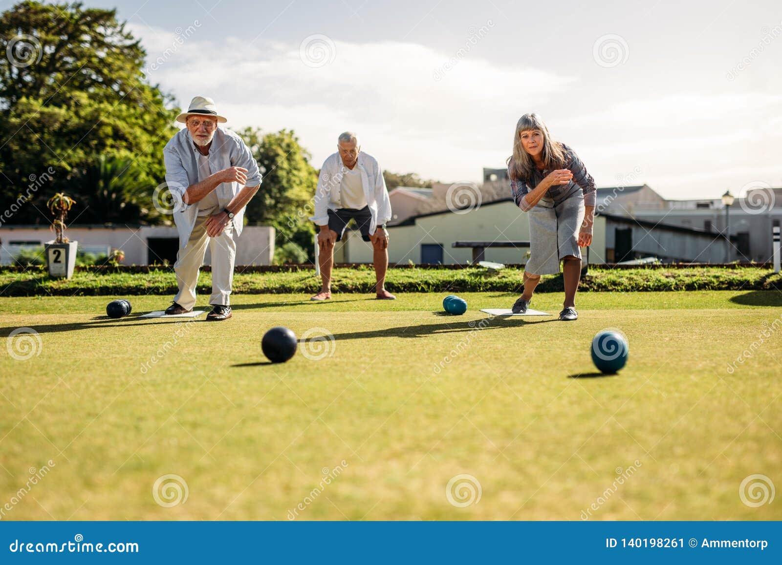 Starszy mężczyzna i kobieta bawić się boules w gazonie