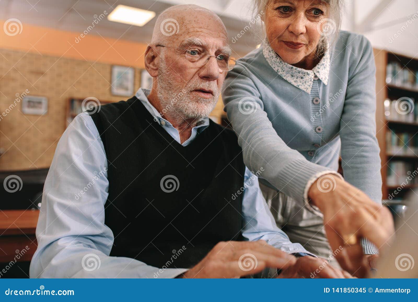 Starszy mężczyzna i kobieta patrzeje ekran komputerowego