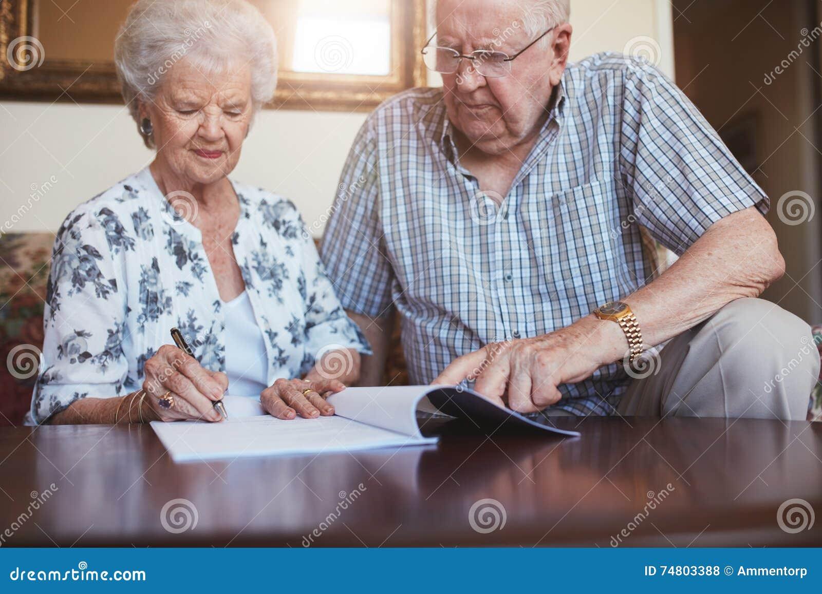 Starszy mąż i żona robi papierkowej robocie wpólnie w domu