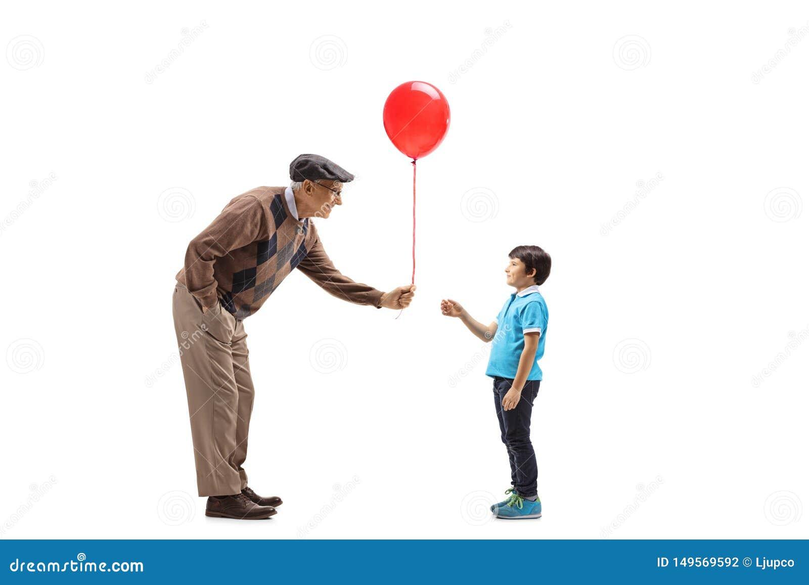 Starszy m??czyzna daje czerwonemu balonowi dziecko