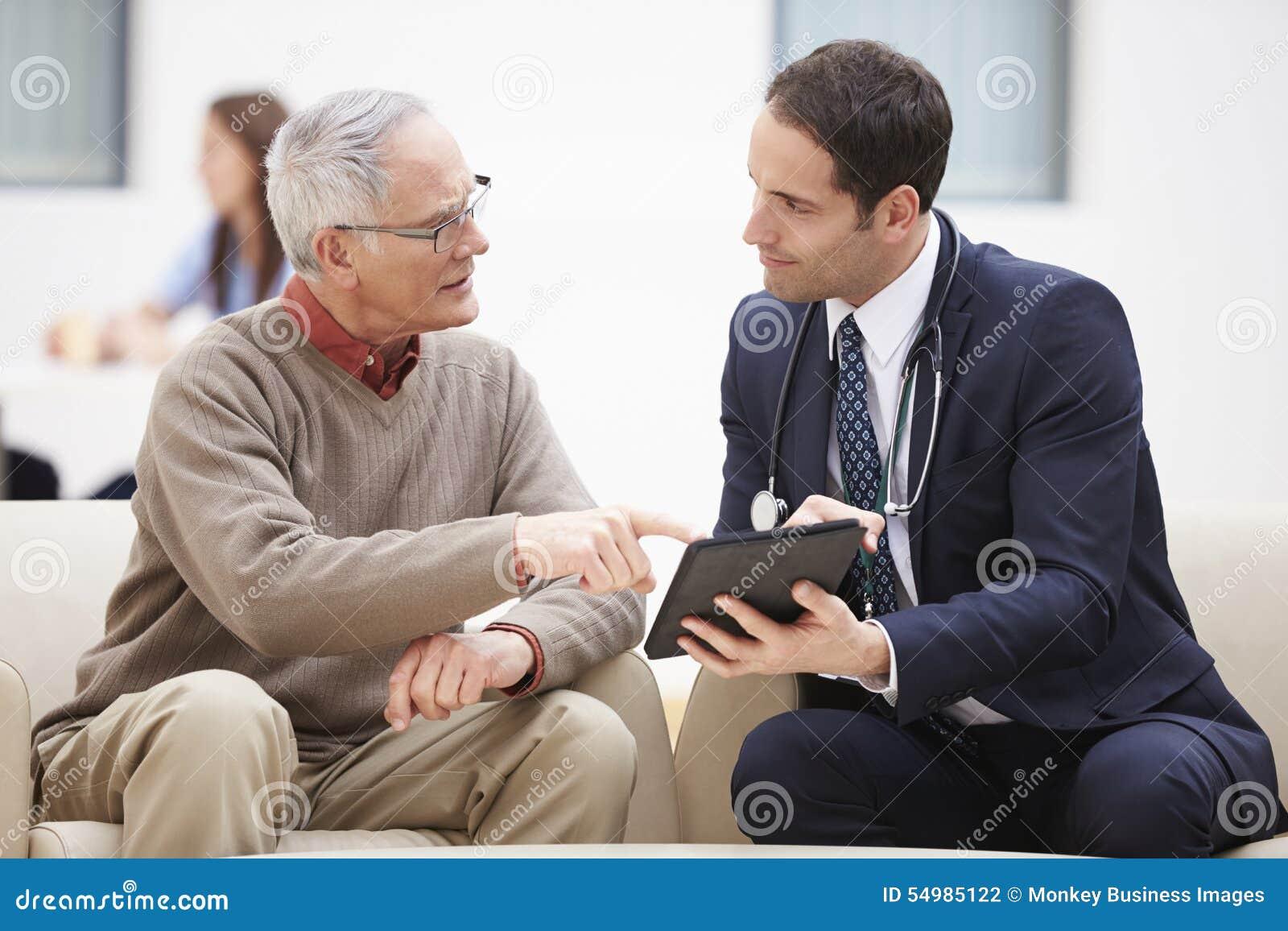 Starszy mężczyzna Dyskutuje rezultaty Z lekarką Na Cyfrowej pastylce