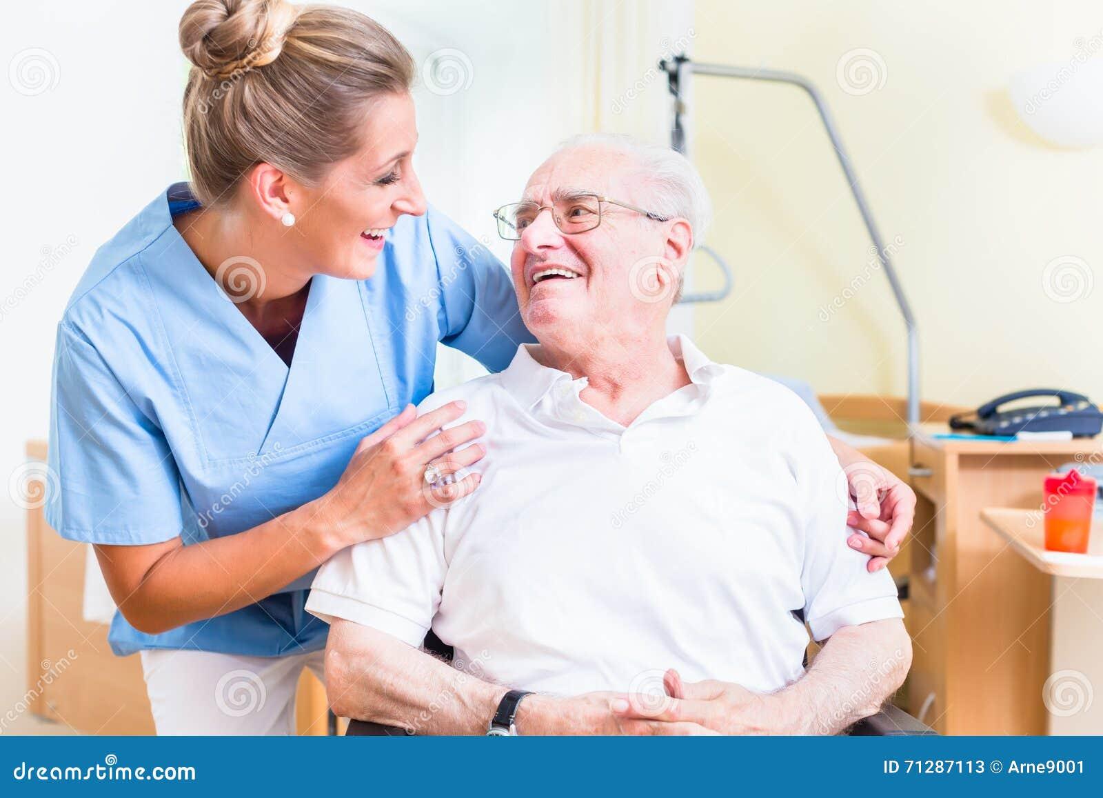 Starszy mężczyzna i starości pielęgniarka w karmiącym domu