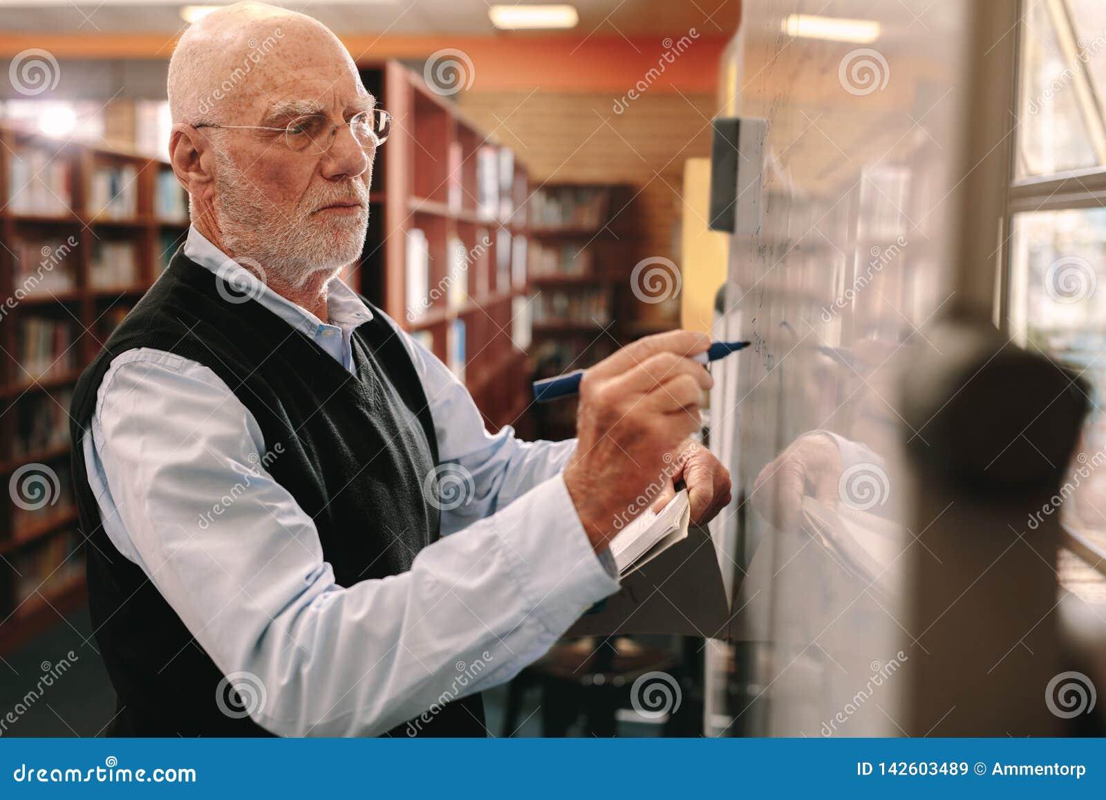 Starszy mężczyzna pisze na sali lekcyjnej desce