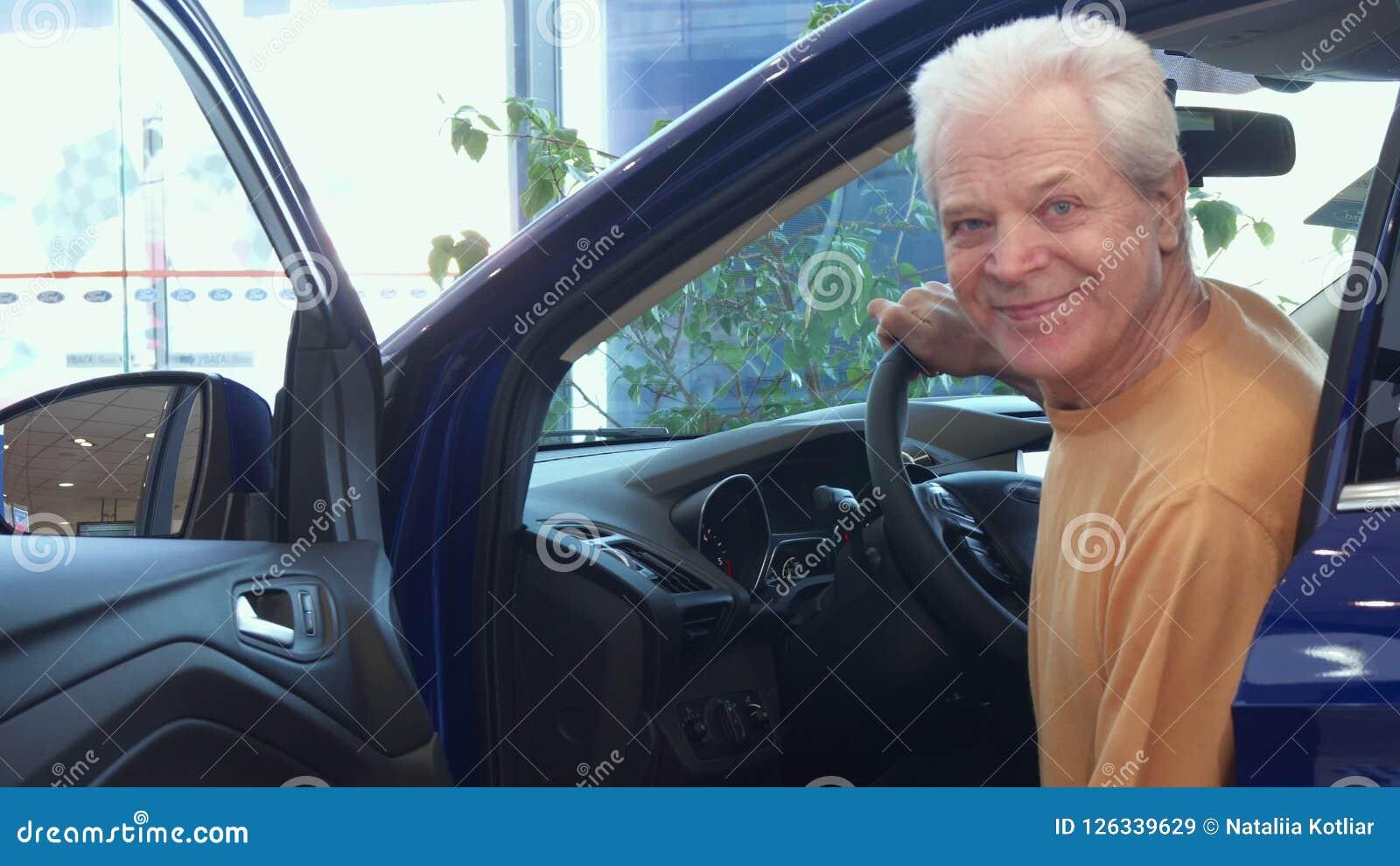 Starszy mężczyzna siedzi puszek w samochód przy przedstawicielstwem handlowym