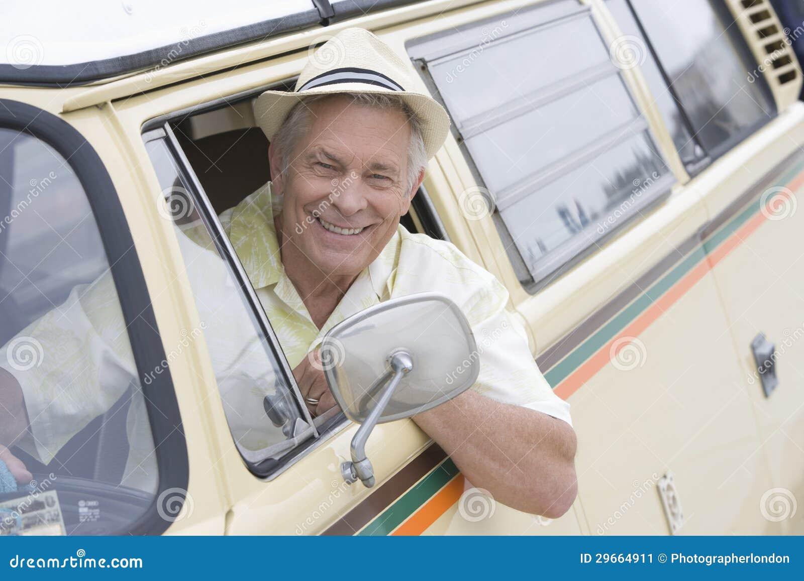 Starszy mężczyzna W kierowcy Seat Patrzeje Przez okno Campervan