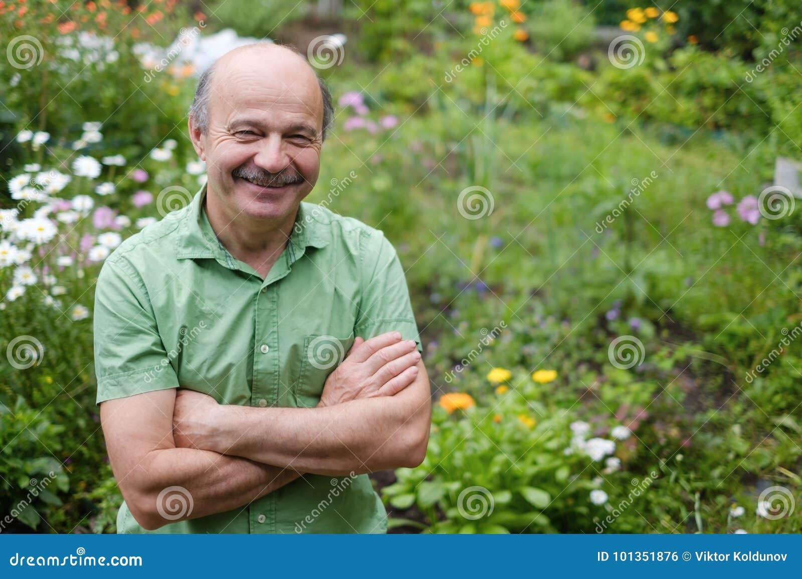Starszy mężczyzna z wąsy i łysym punktem w zielonej koszulce stoi wśród kwiatów w lato ogródzie, ręki
