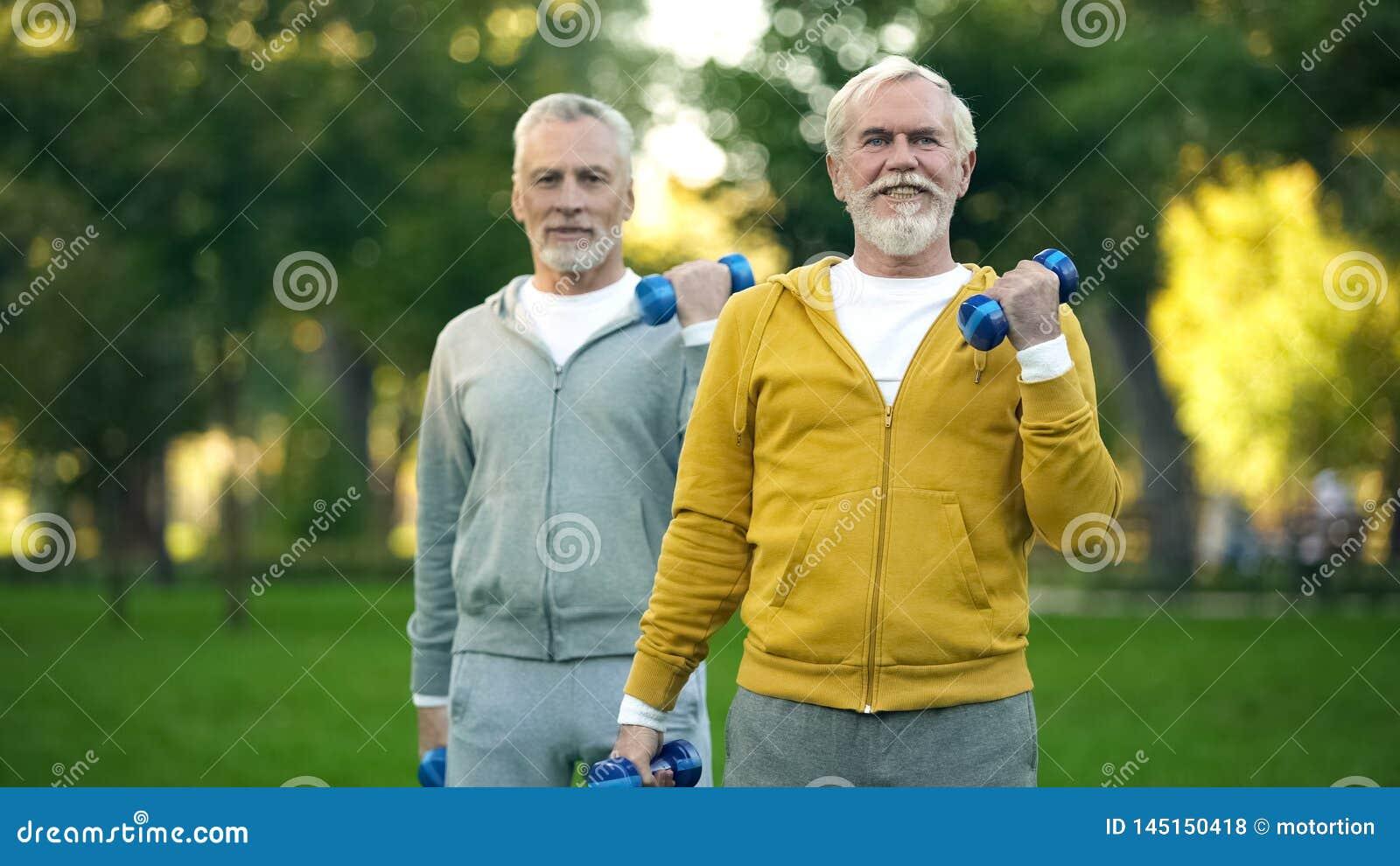 Starszy m??czy?ni podnosi dumbbells w parku, przyjaciele opracowywa wp?lnie, sprawno?? fizyczna