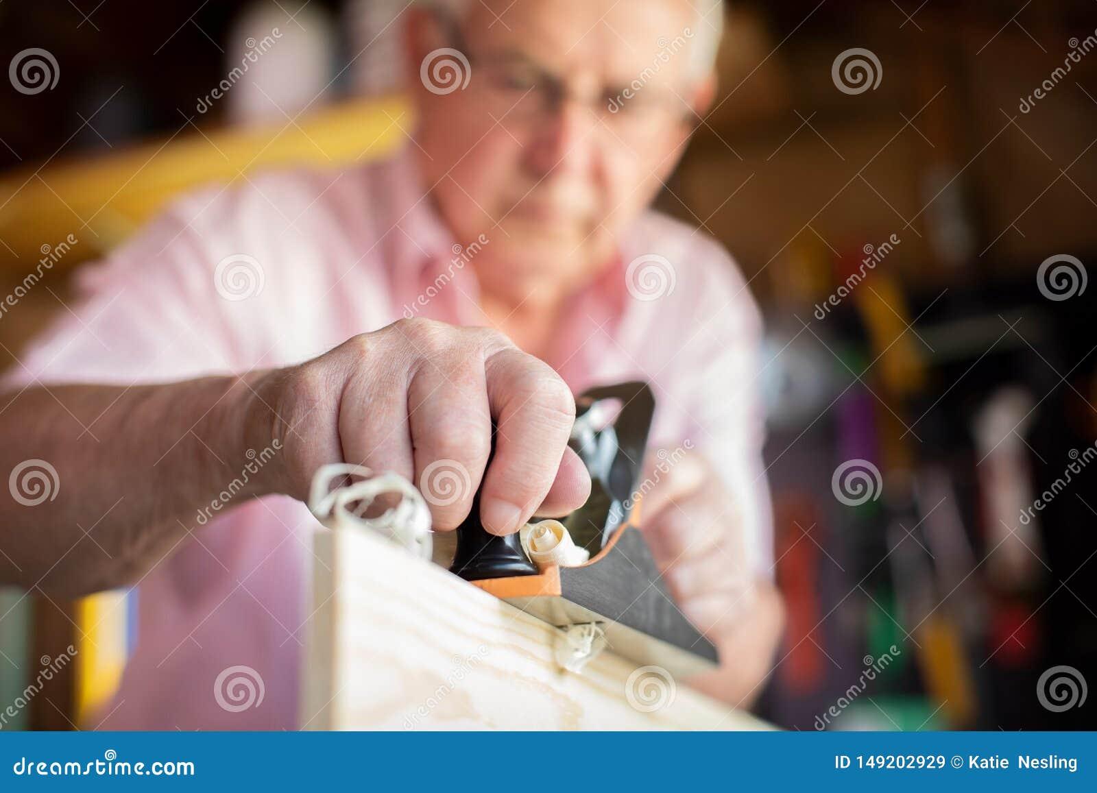 Starszy m??czyzna Cieszy si? ciesielki heblowania drewno W ogr?d jacie