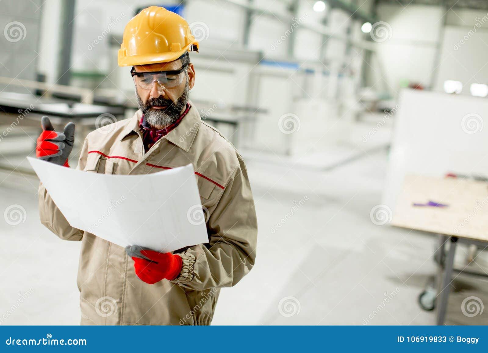 Starszy nadzorca patrzeje projest w fabryce