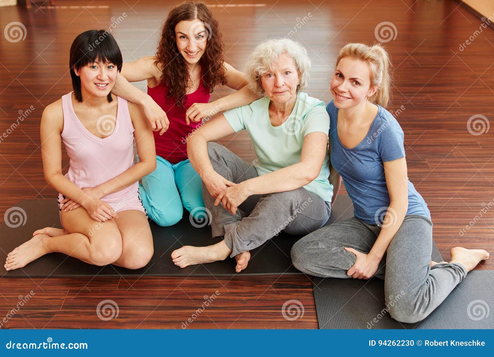 Starszy obywatel i młode kobiety w joga klasie