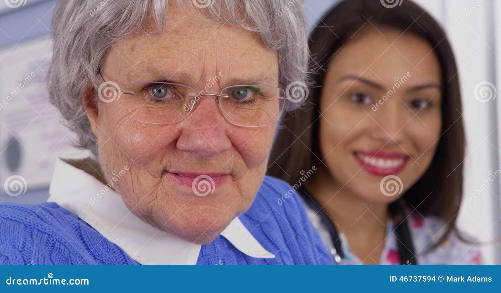 Starszy pacjent i meksykanina opiekun patrzeje kamerę