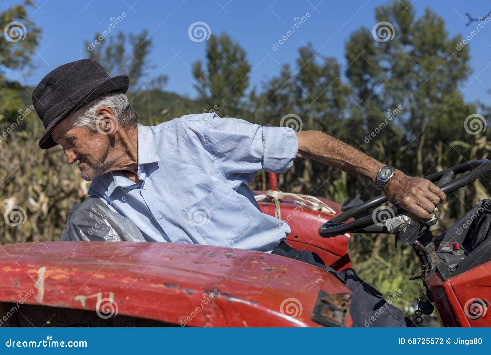 Starszy rolnik używa starego ciągnika orać jego gruntowego